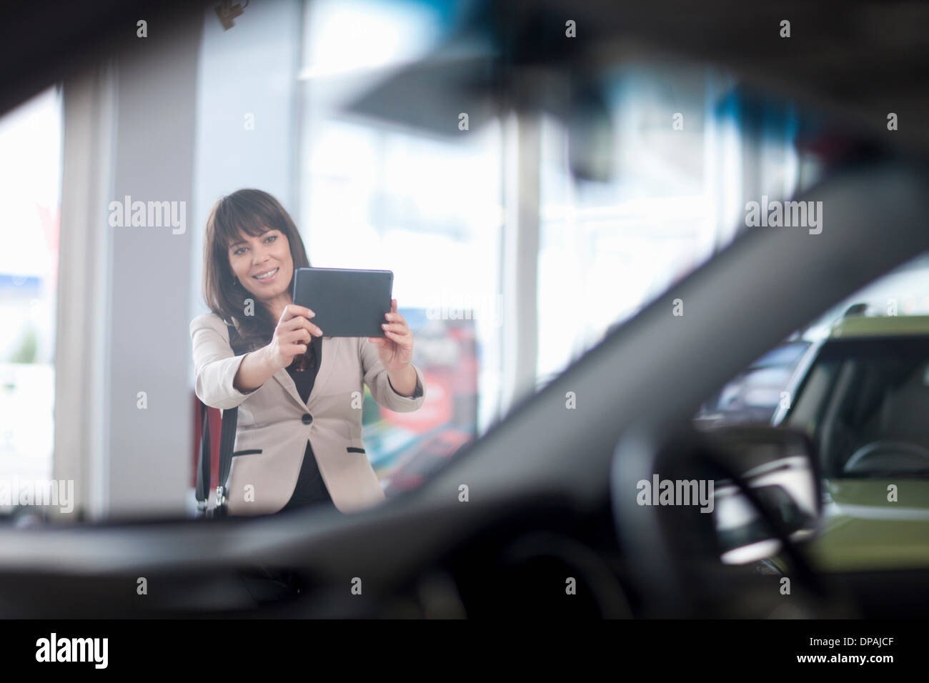 Mid adult woman photographing car in showroom - Stock Image