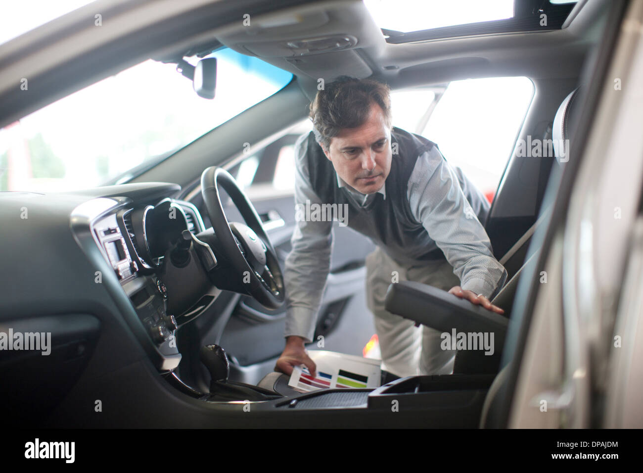Mid adult man checking arm rest in car showroom - Stock Image