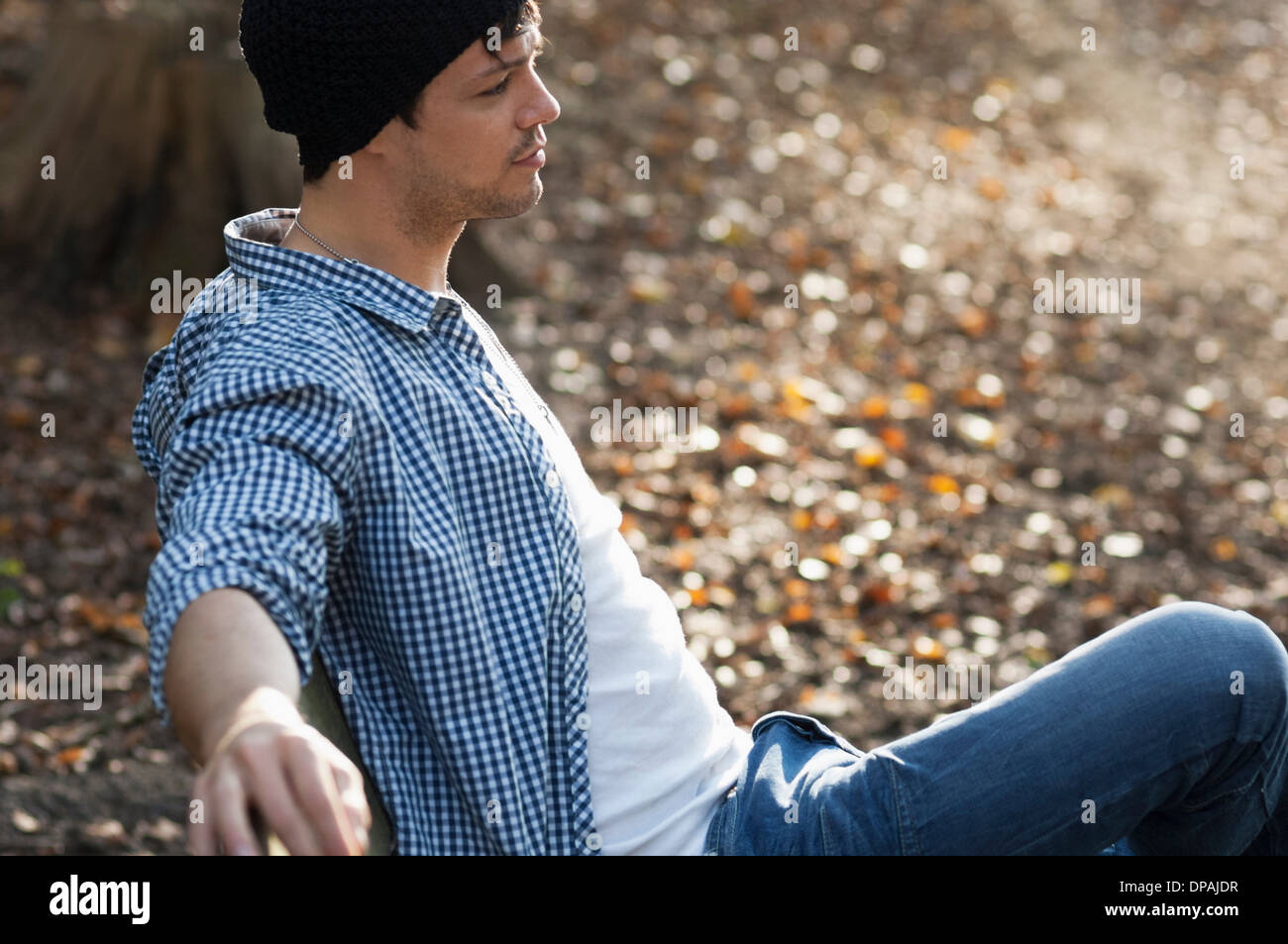 Portrait of man sitting on bench in autumn - Stock Image