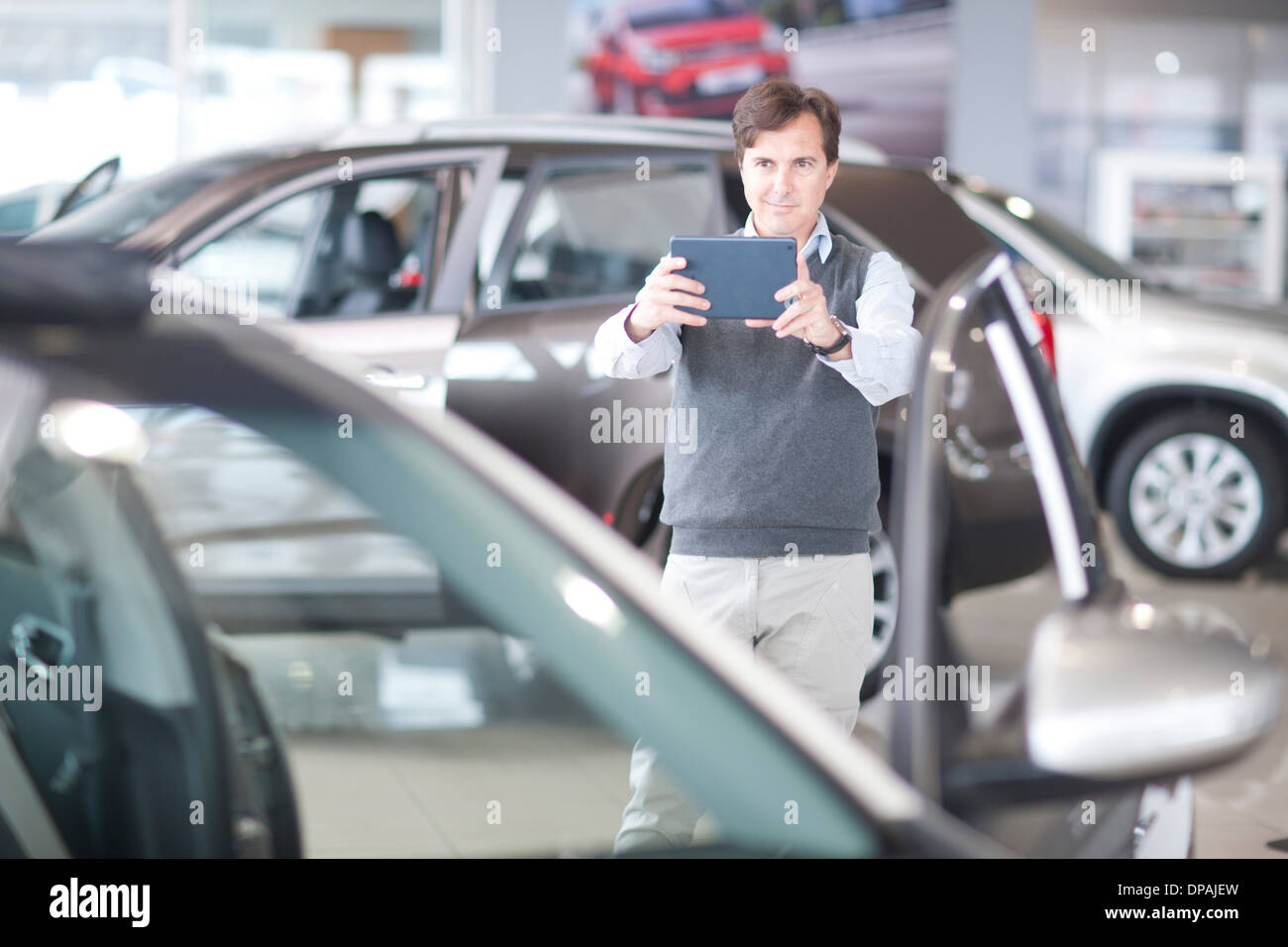 Mid adult man photographing car in showroom - Stock Image