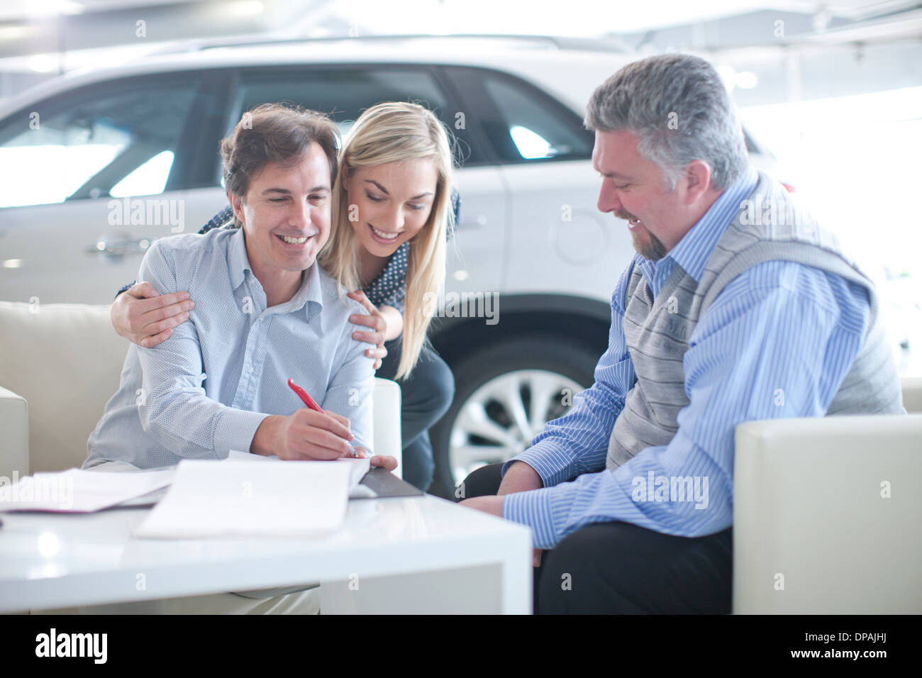 Car salesman and couple signing contract in car showroom - Stock Image