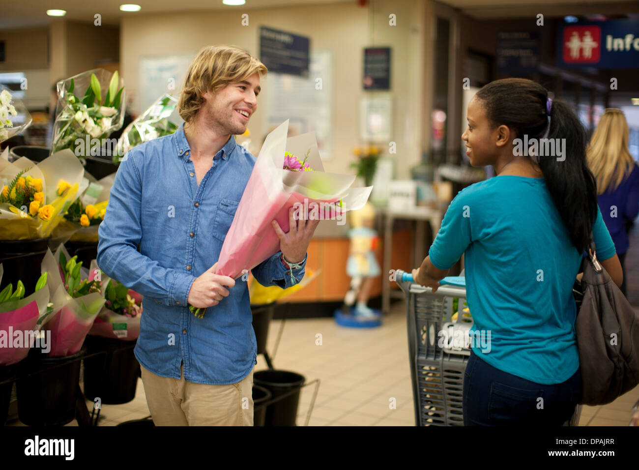 Young man selecting bunch of flowers whilst shopping - Stock Image
