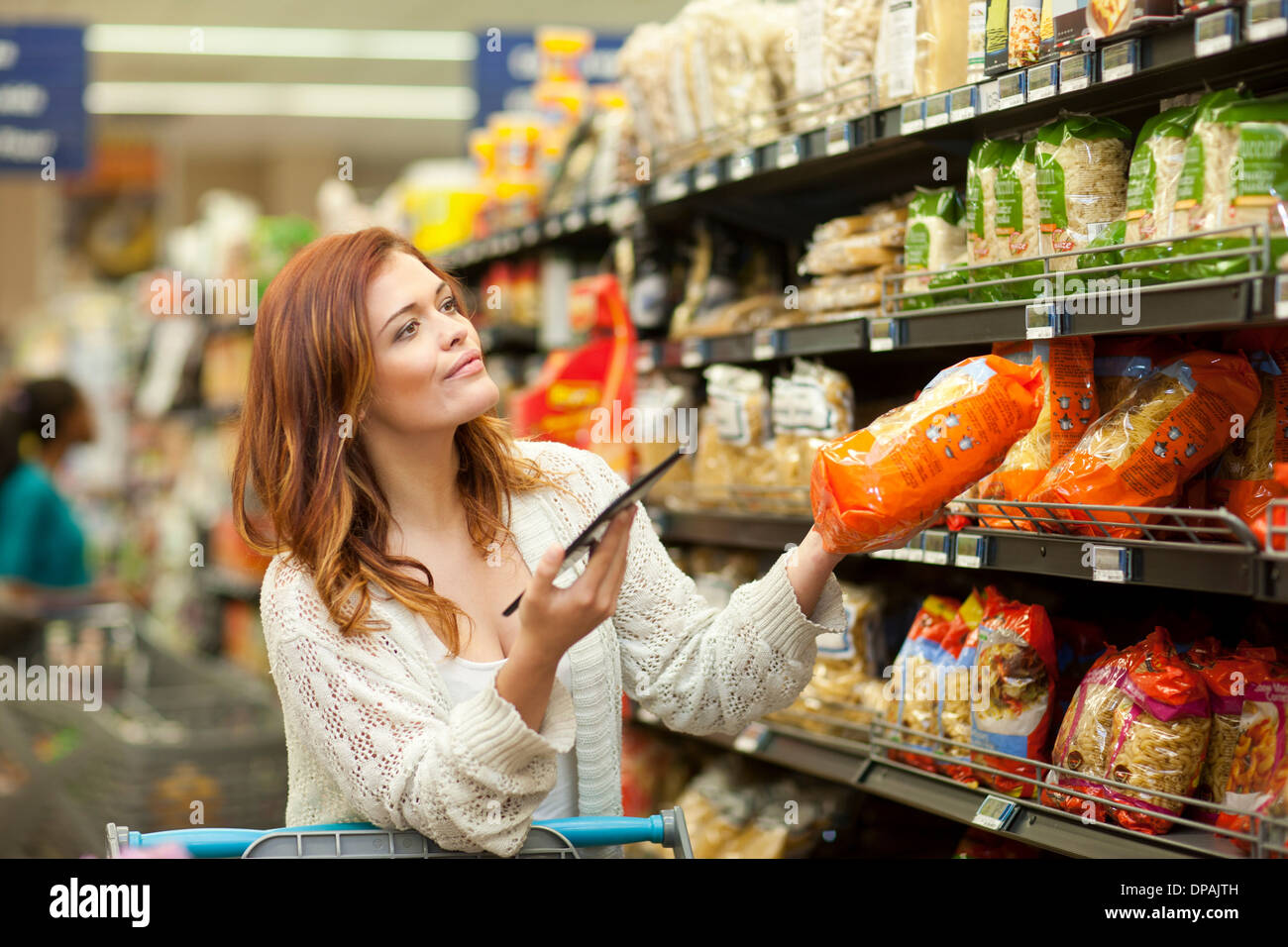 Female shopper with digital tablet in supermarket - Stock Image
