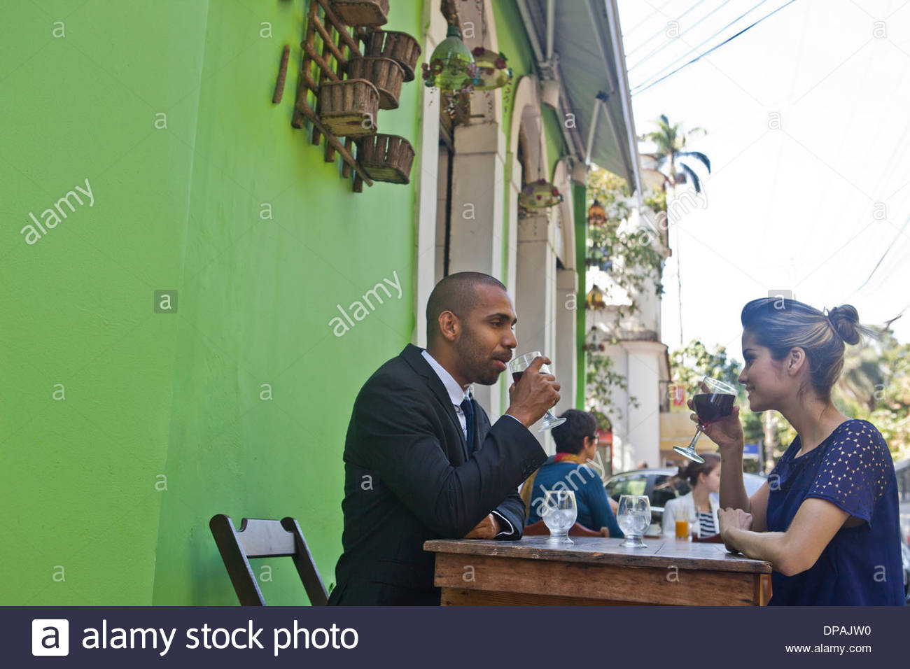Man and woman having wine outside cafe - Stock Image
