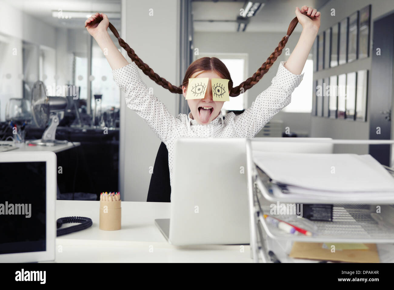 Girl in office with adhesive notes covering eyes holding plaits - Stock Image