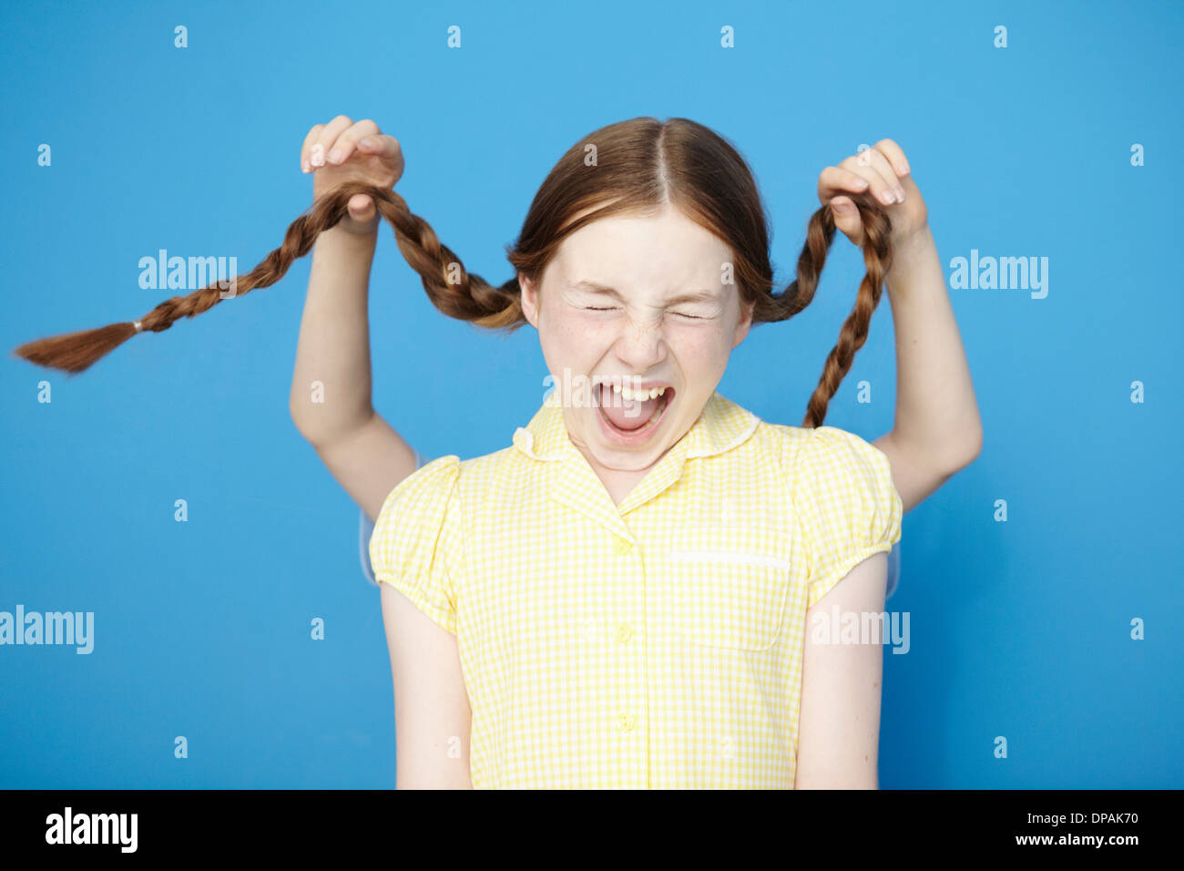 Girl wearing yellow school dress, boy behind pulling her plaits - Stock Image