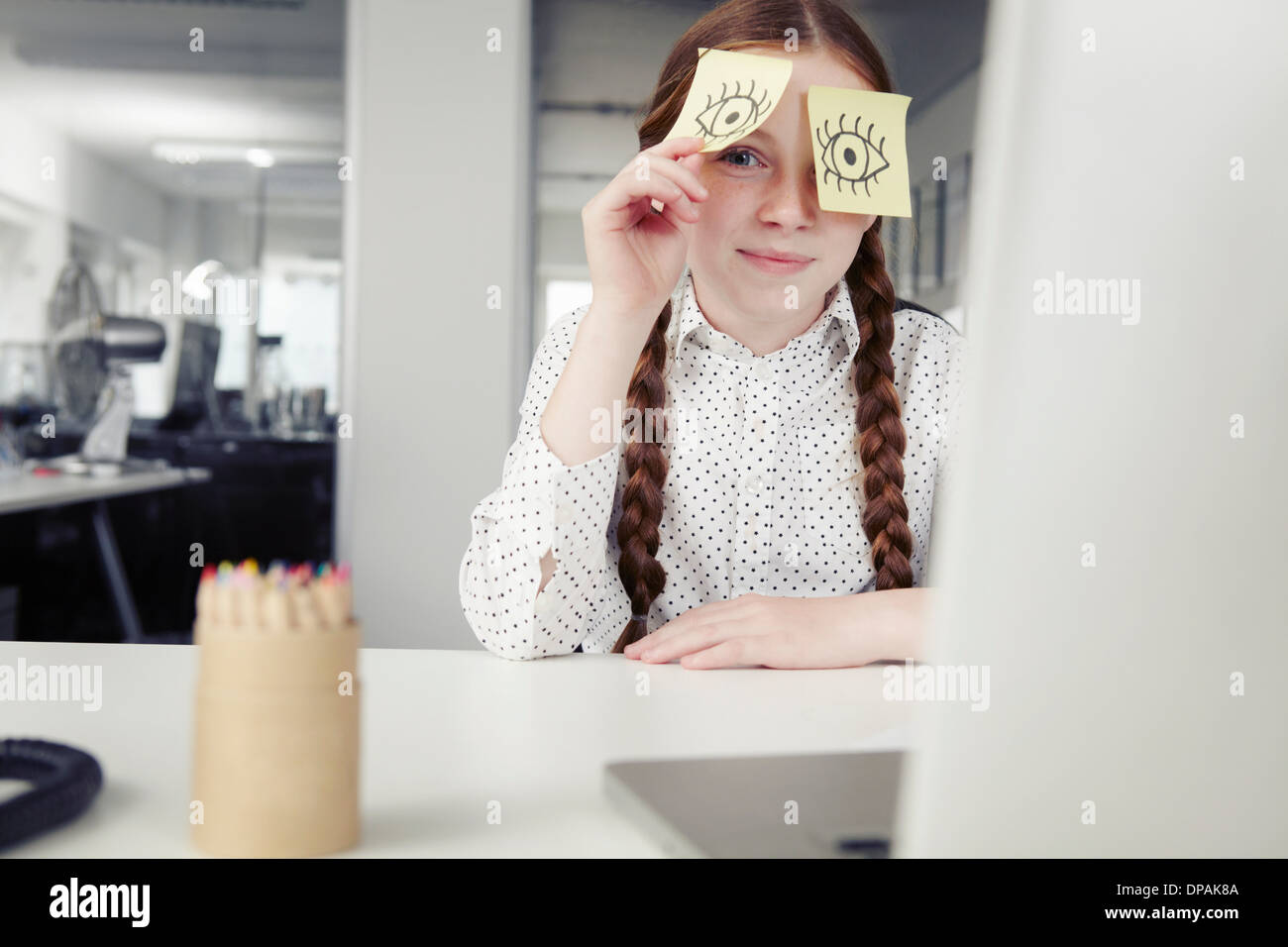 Girl in office with adhesive notes covering eyes, peeking - Stock Image