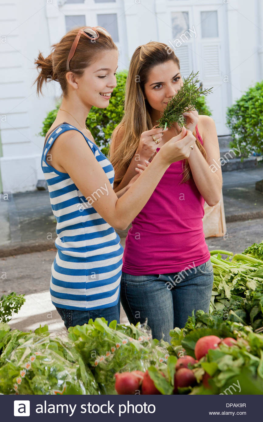 Two young women buying fresh herbs in market - Stock Image