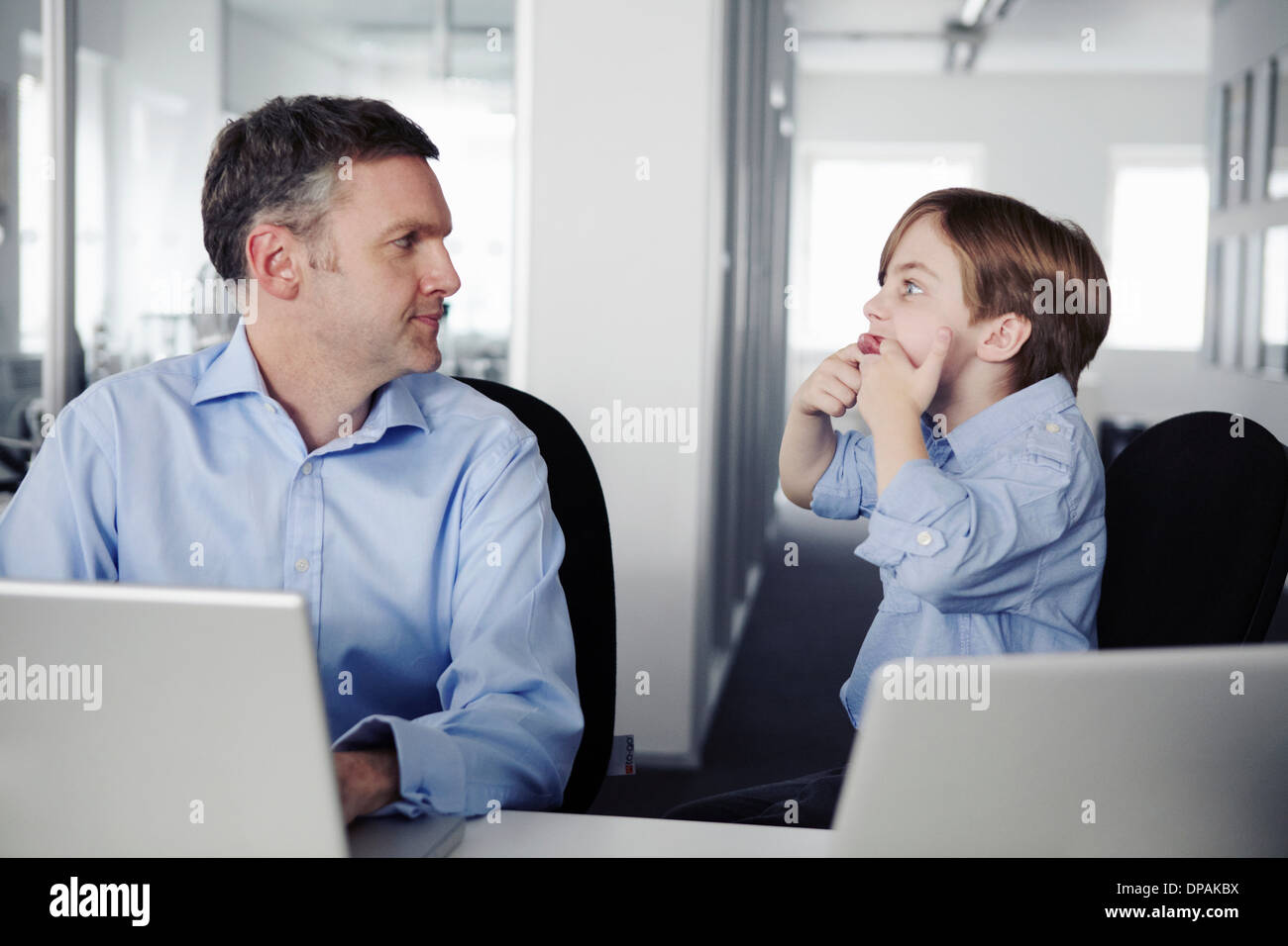 Father using laptop, son pulling faces - Stock Image