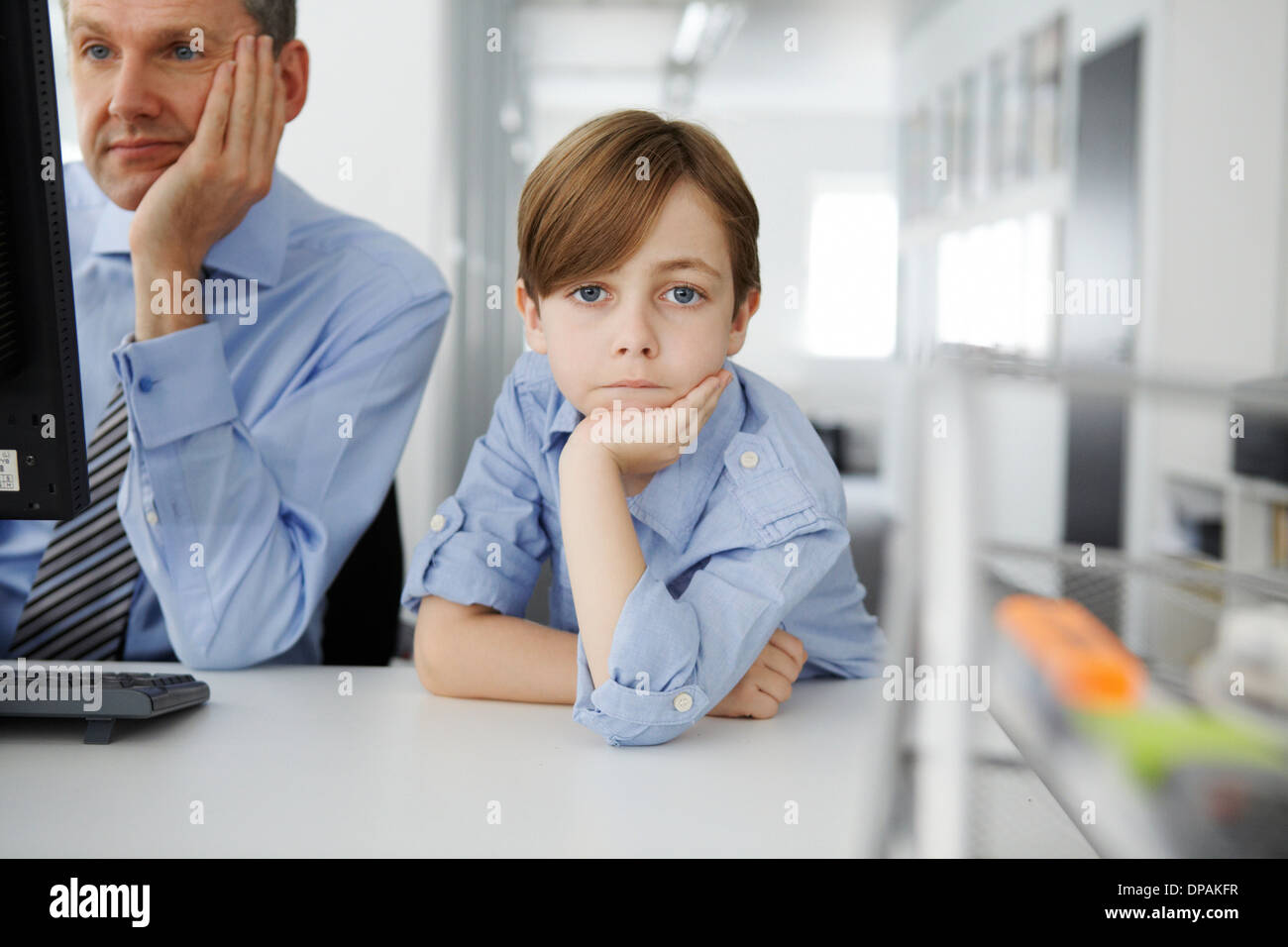 Boy leaning on elbow, father using computer - Stock Image