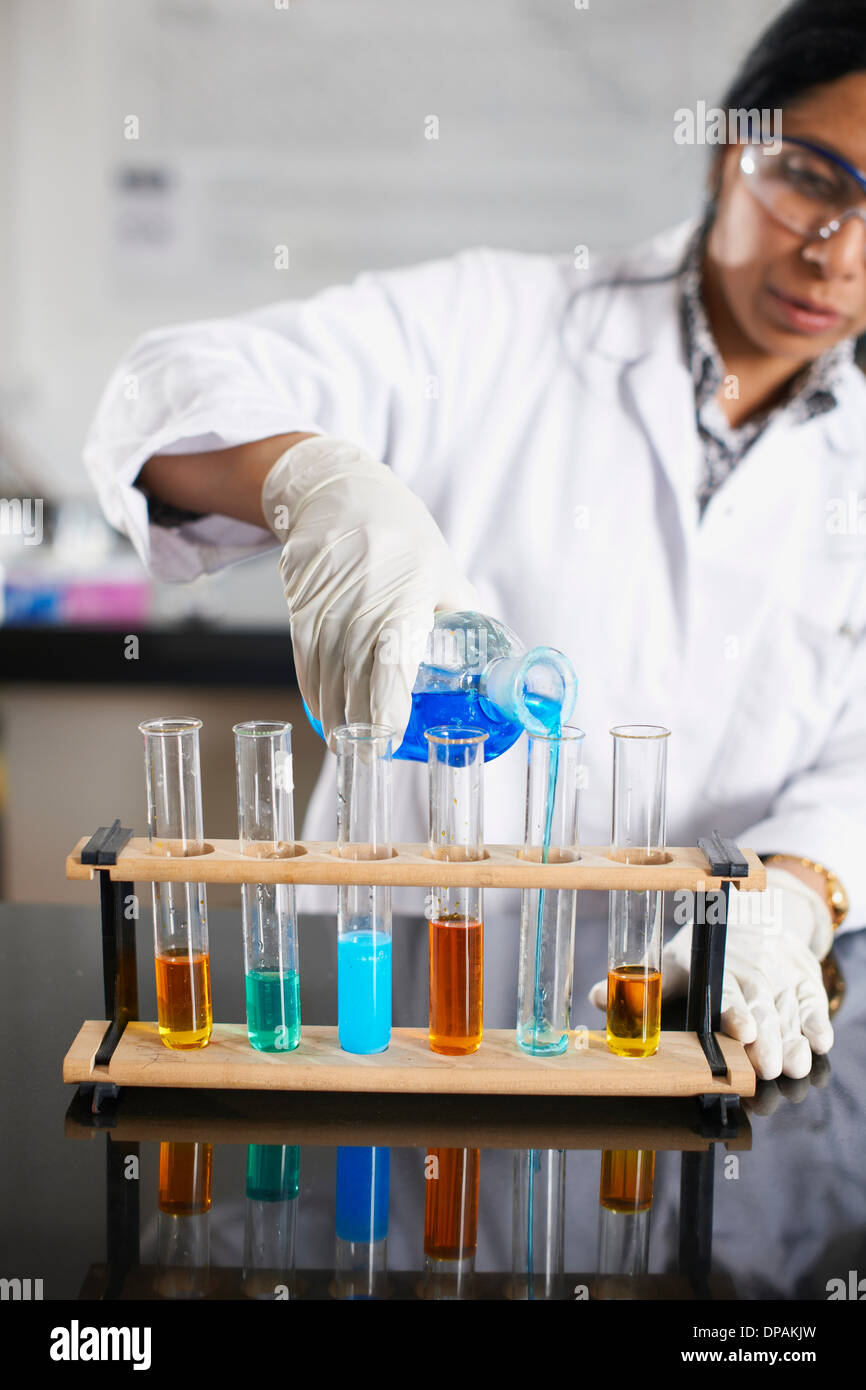 Chemistry teacher pouring chemicals into test tubes - Stock Image
