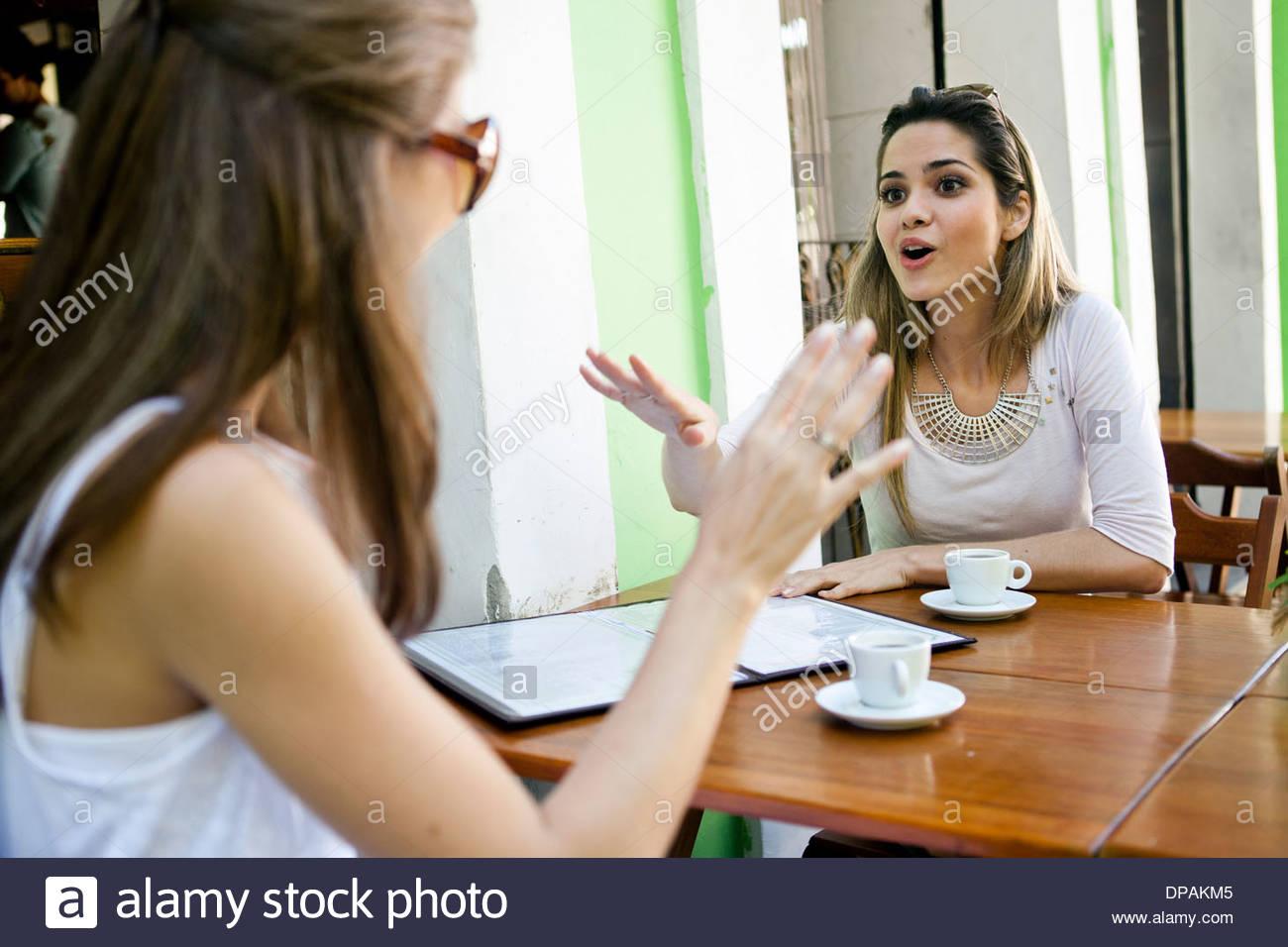 Female friends having conversation outside cafe - Stock Image
