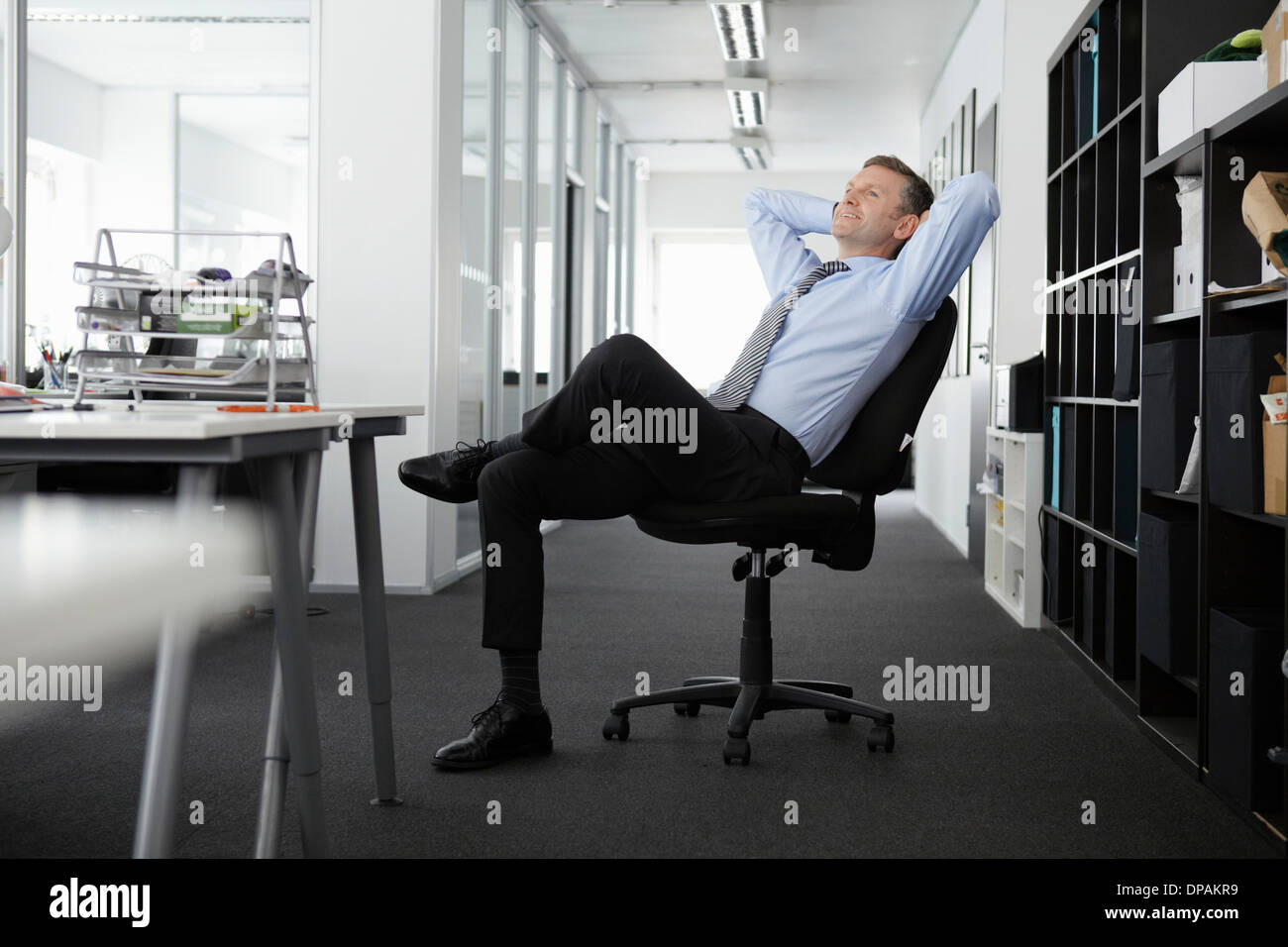 Mature businessman leaning back in office chair - Stock Image