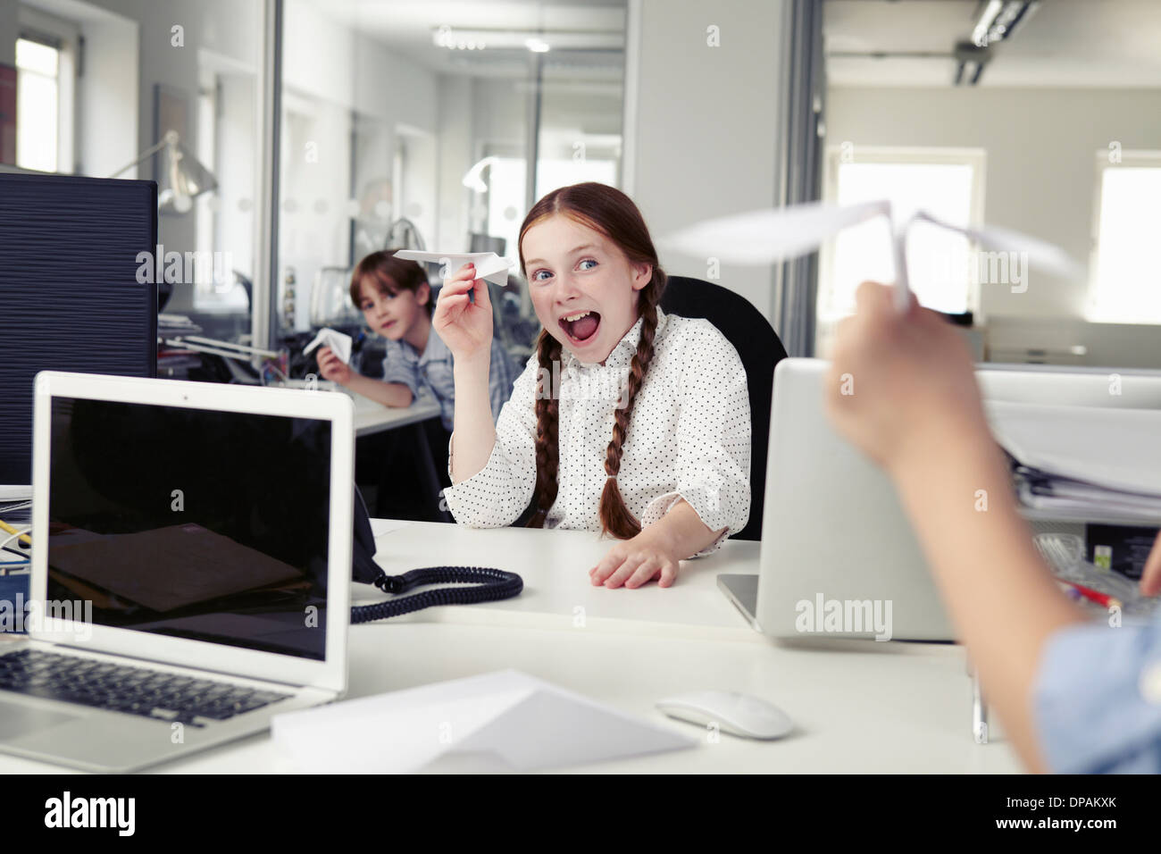 Children holding paper airplanes in office - Stock Image