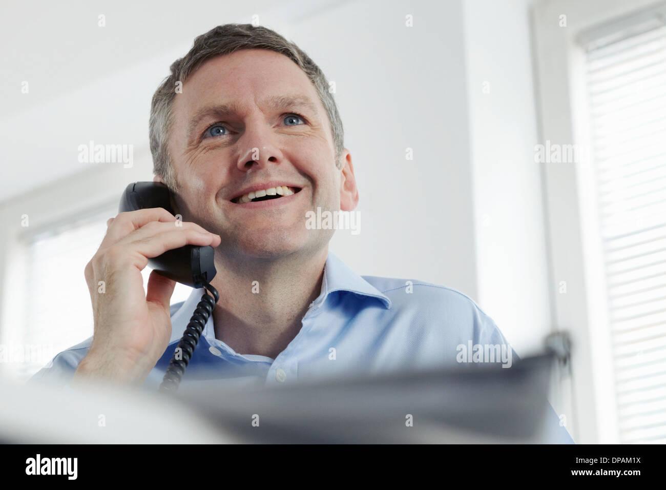 Mature businessman on landline phone - Stock Image