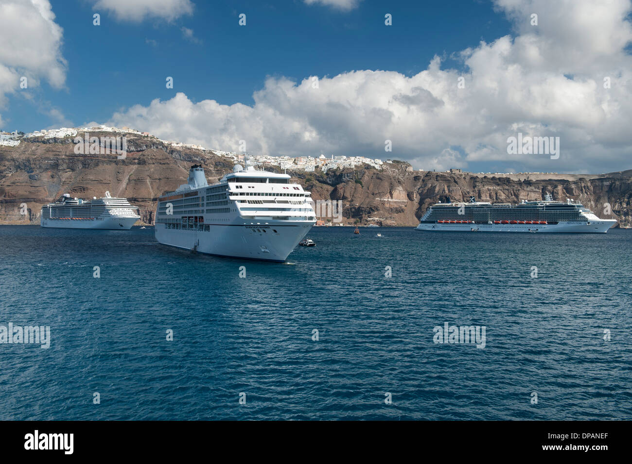 View of the village of Fira and cruise ships anchored off the coast of the Greek island of Santorini. - Stock Image