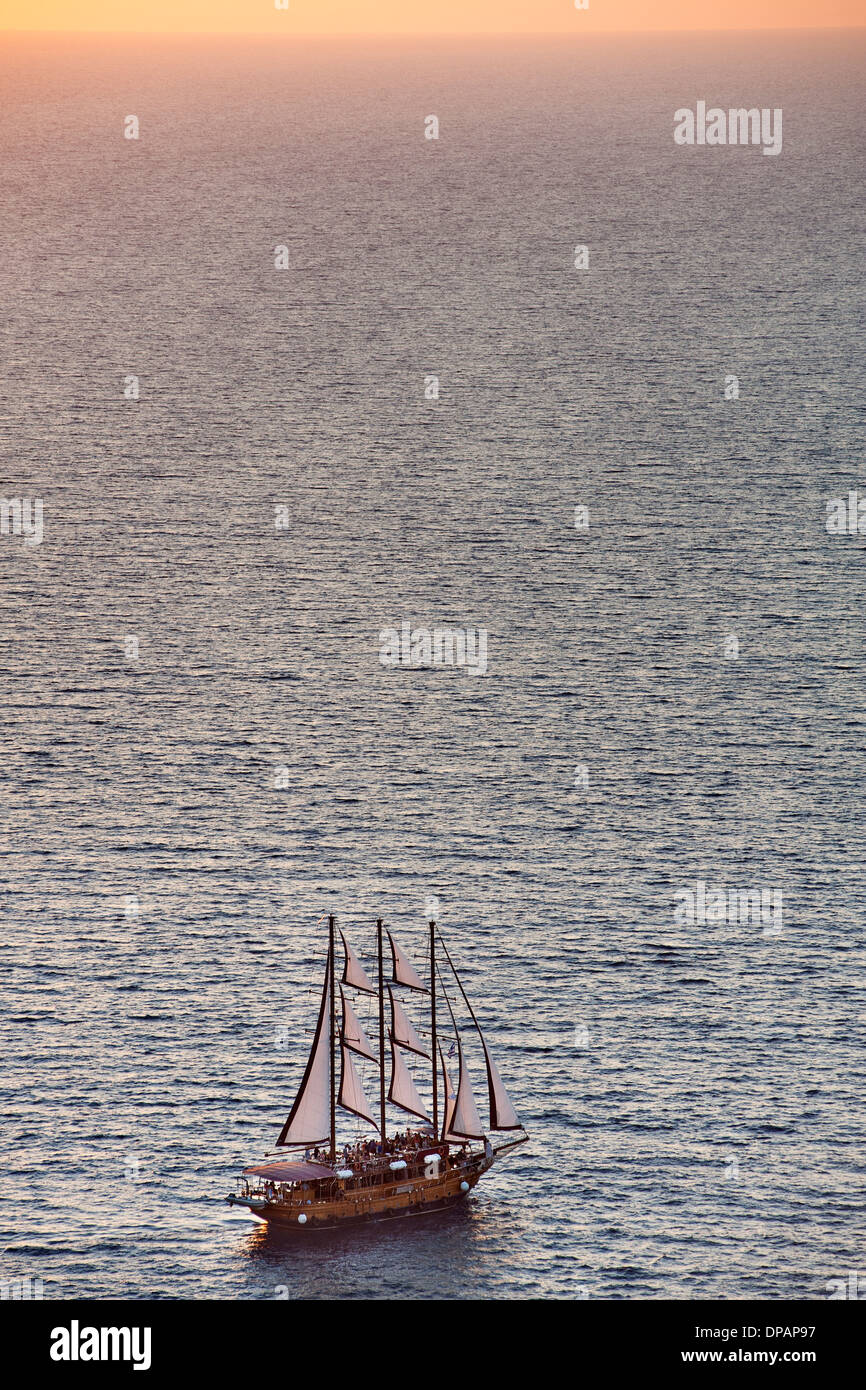 Sailing boat off the coast of Santorini in Greece. - Stock Image