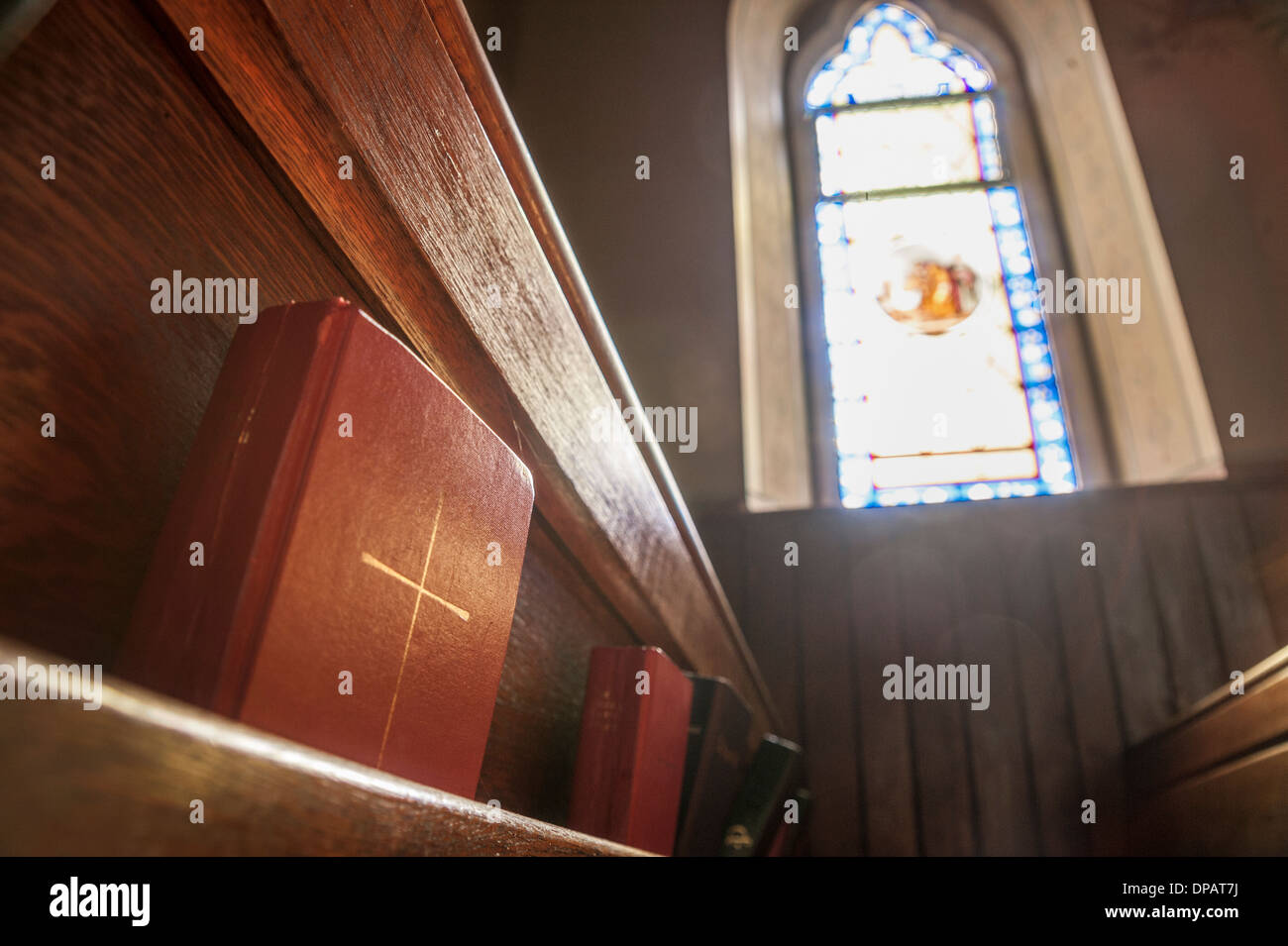 Church pew and stained glass window light - Stock Image