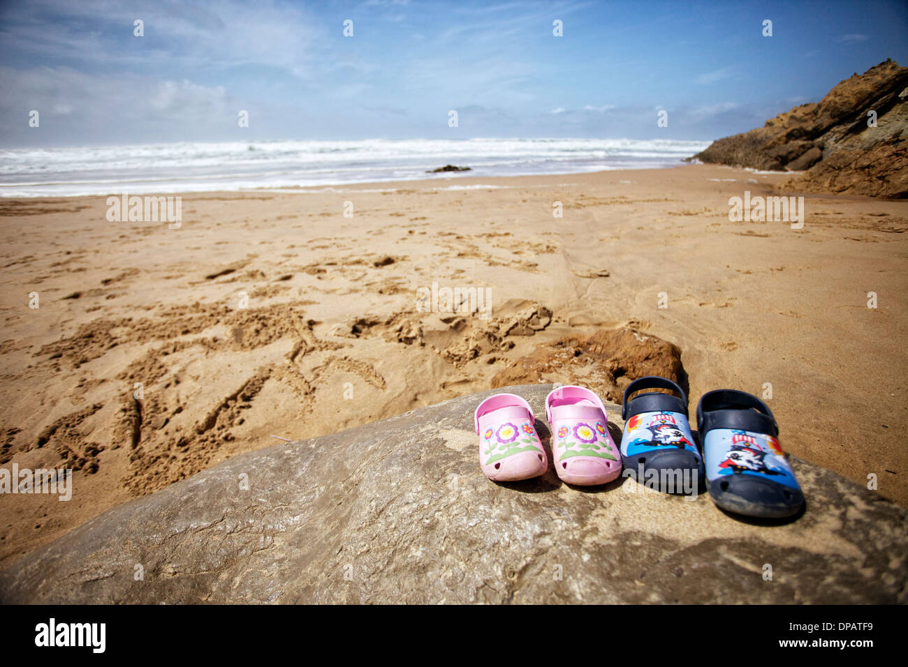 d990db93c Childrens  crocs  shoes on a rock on a beach with waves and blue skies