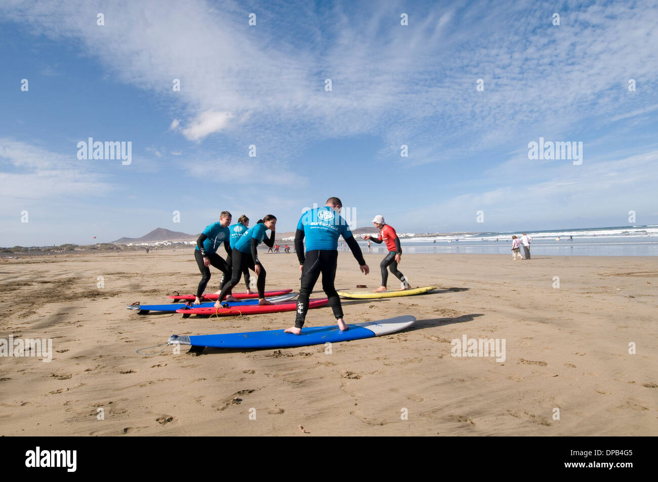 surfing lesson lessons learning to stand up on surf board boards surfboards beach playa famara lanzarote beach beaches canary is - Stock Image