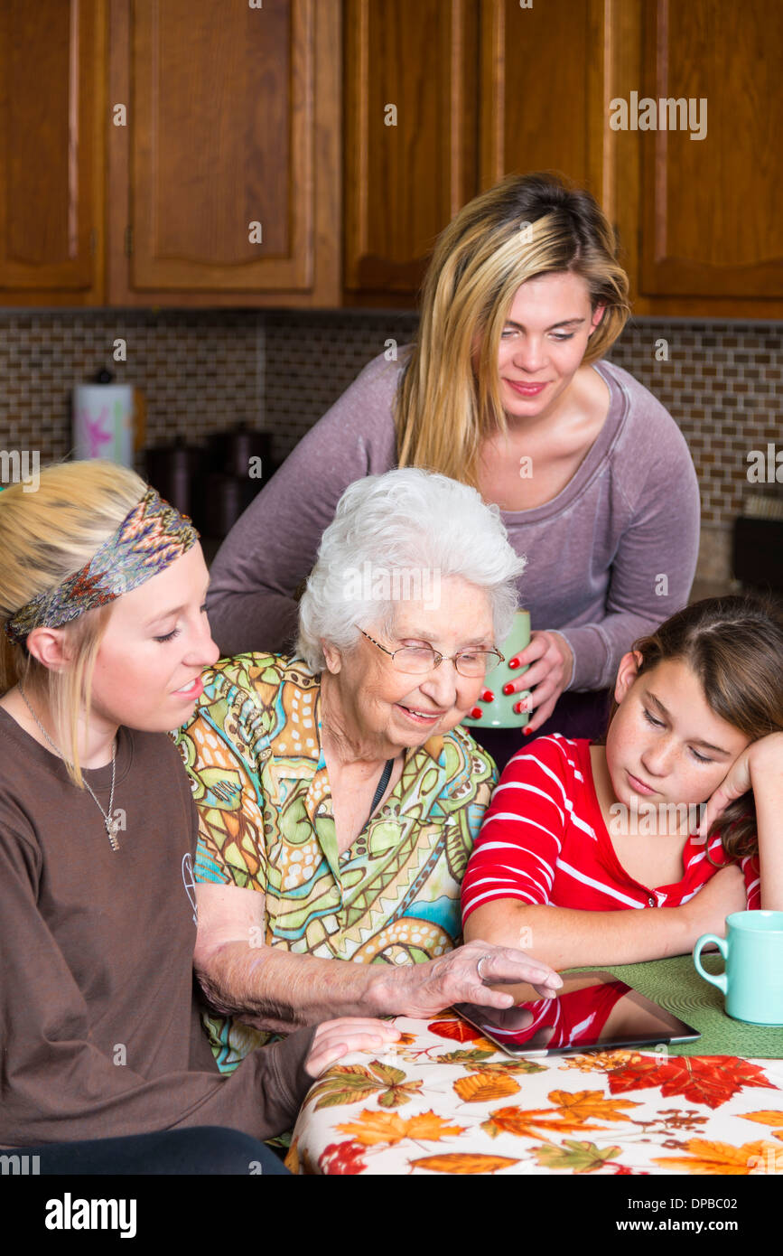 Aged woman with tablet computer amid her family - Stock Image