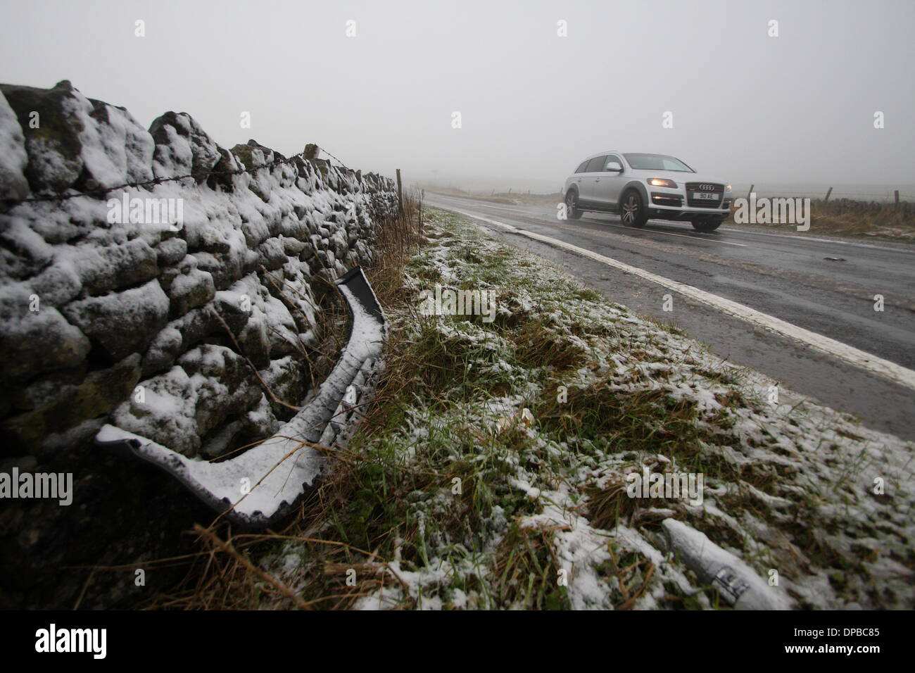 Peak District, Derbyshire, UK. 11th January 2014. 11 Jan 2014  a car bumper lies by the side of the road as fog and snow sweep over the A6187 near Castleton making for tricky driving conditions after overnight snowfall hit stretches of high ground iin Derbyshire's Peak District. Credit:  Matthew Taylor/Alamy Live News - Stock Image