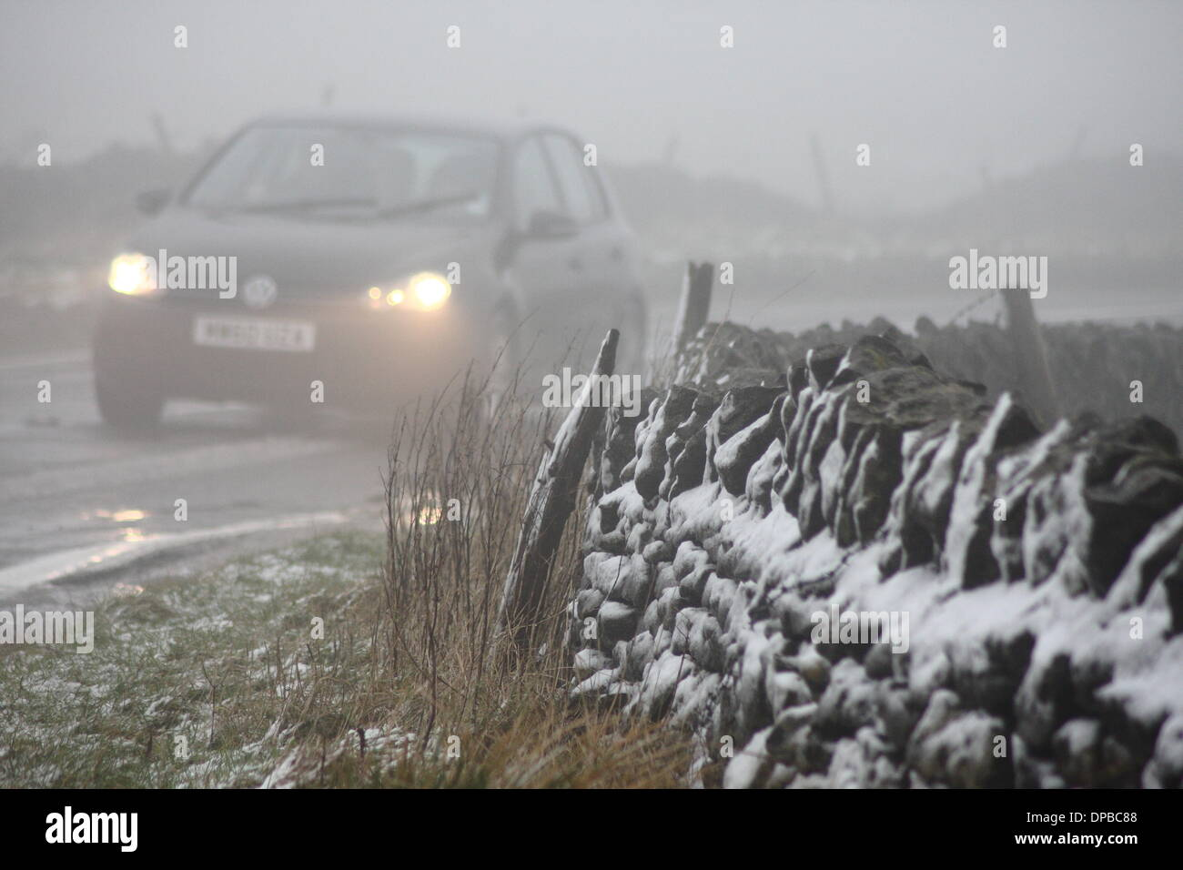 Peak District, Derbyshire, UK. 11th January 2014.  11 Jan 2014. Wintry conditions on the A6187 near Castleton made for extra tricky driving conditions after overnight snowfall hit stretches of high ground iin Derbyshire's Peak District. Credit:  Matthew Taylor/Alamy Live News - Stock Image