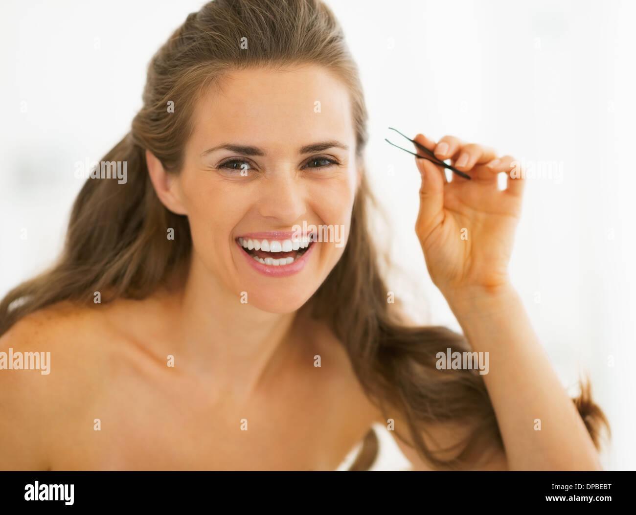 Happy young woman with tweezers - Stock Image