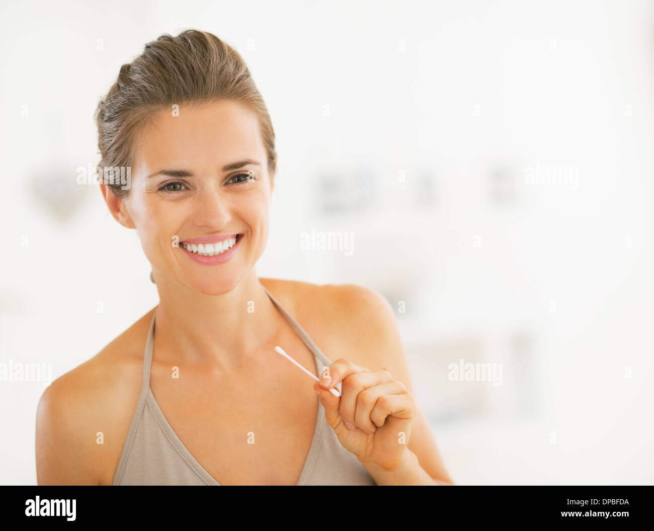 Young woman with cotton swab in bathroom - Stock Image