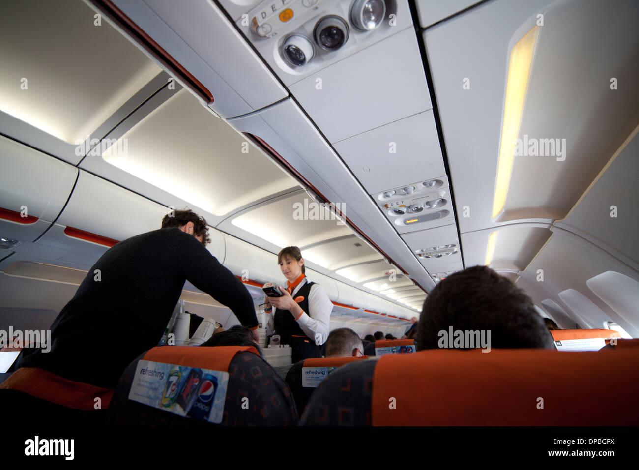 Easyjet airbus cabin crew stewardess bringing drinks to travelers - Stock Image