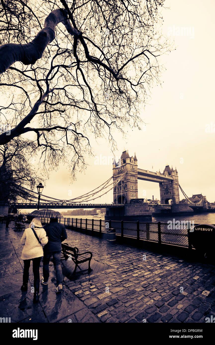 Couple walking towards Tower Bridge under the rain. City of London, Uk - Stock Image