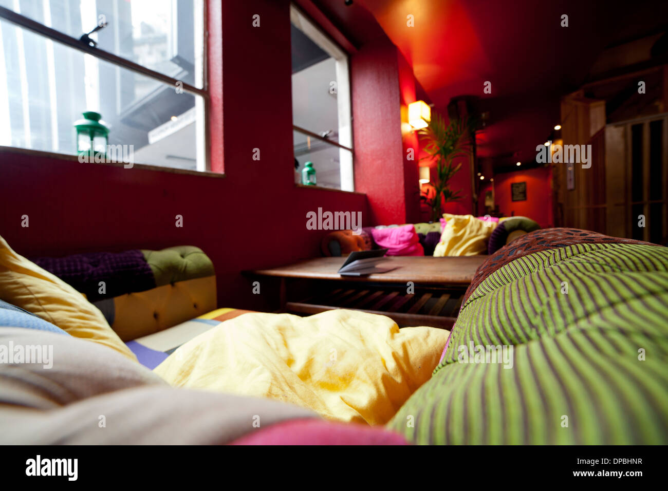 Patchwork comfortable sofas and red painted walls - Stock Image