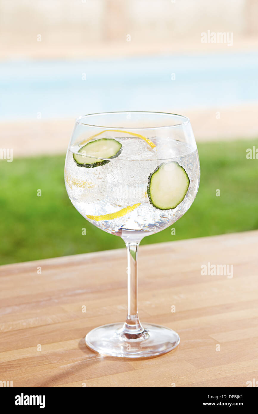 Cucumber gin and tonic cocktail on poolside bar - Stock Image