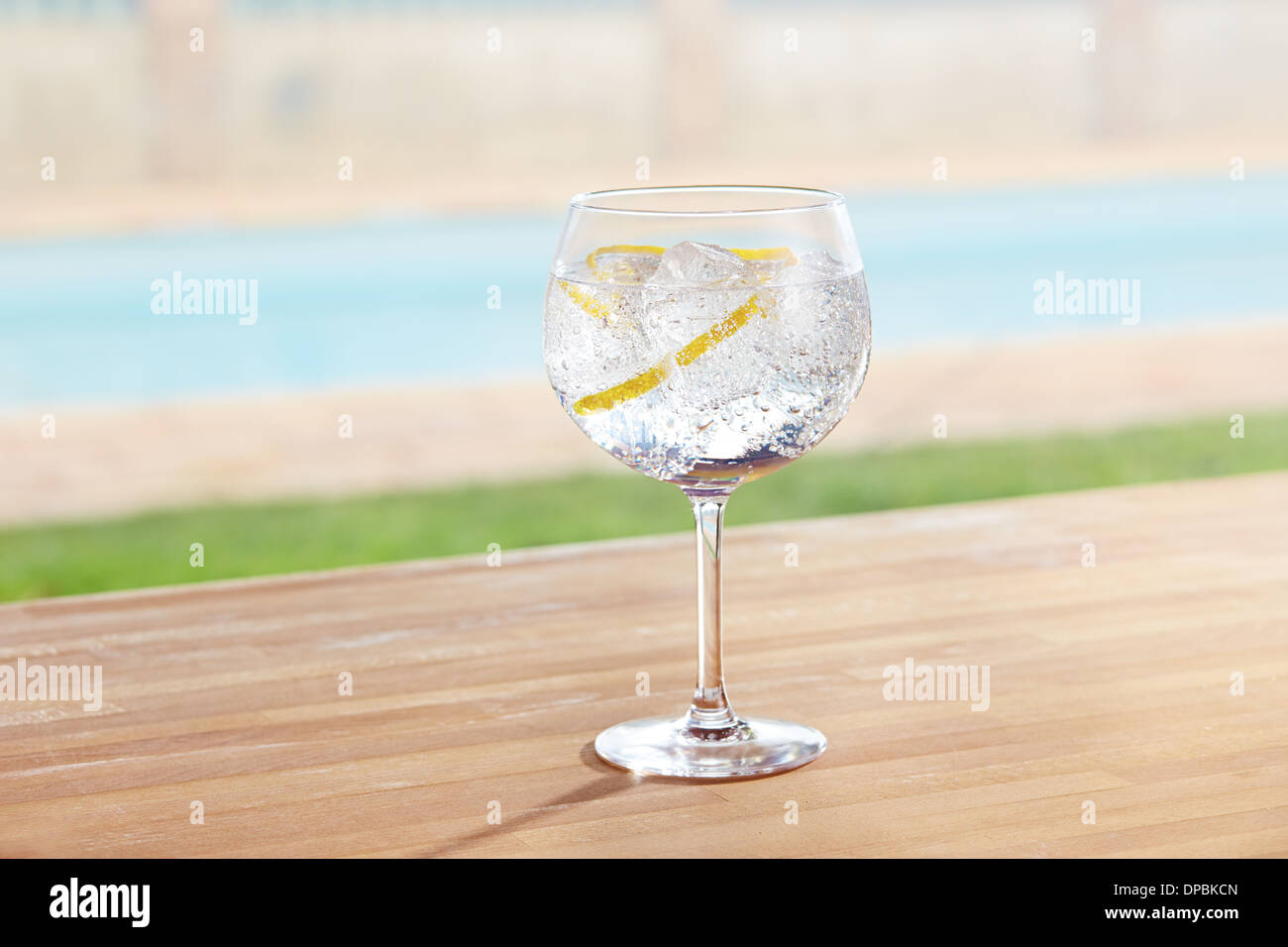 Gin and tonic cocktail on poolside bar - Stock Image