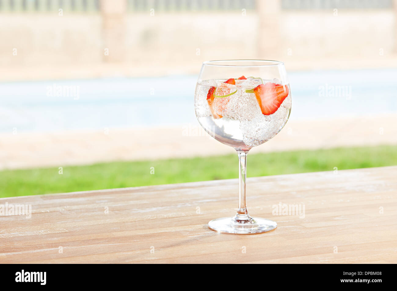 Strawberry gin and tonic cocktail on poolside bar - Stock Image