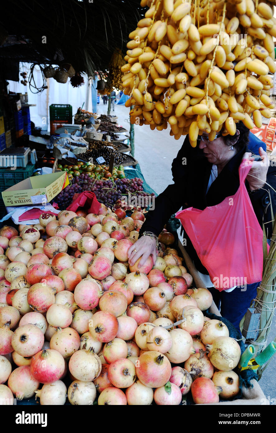 shopper buying pomegranates at fruitstand in the annual All Saints Market in Cocentaina, Alicante province, Spain Stock Photo
