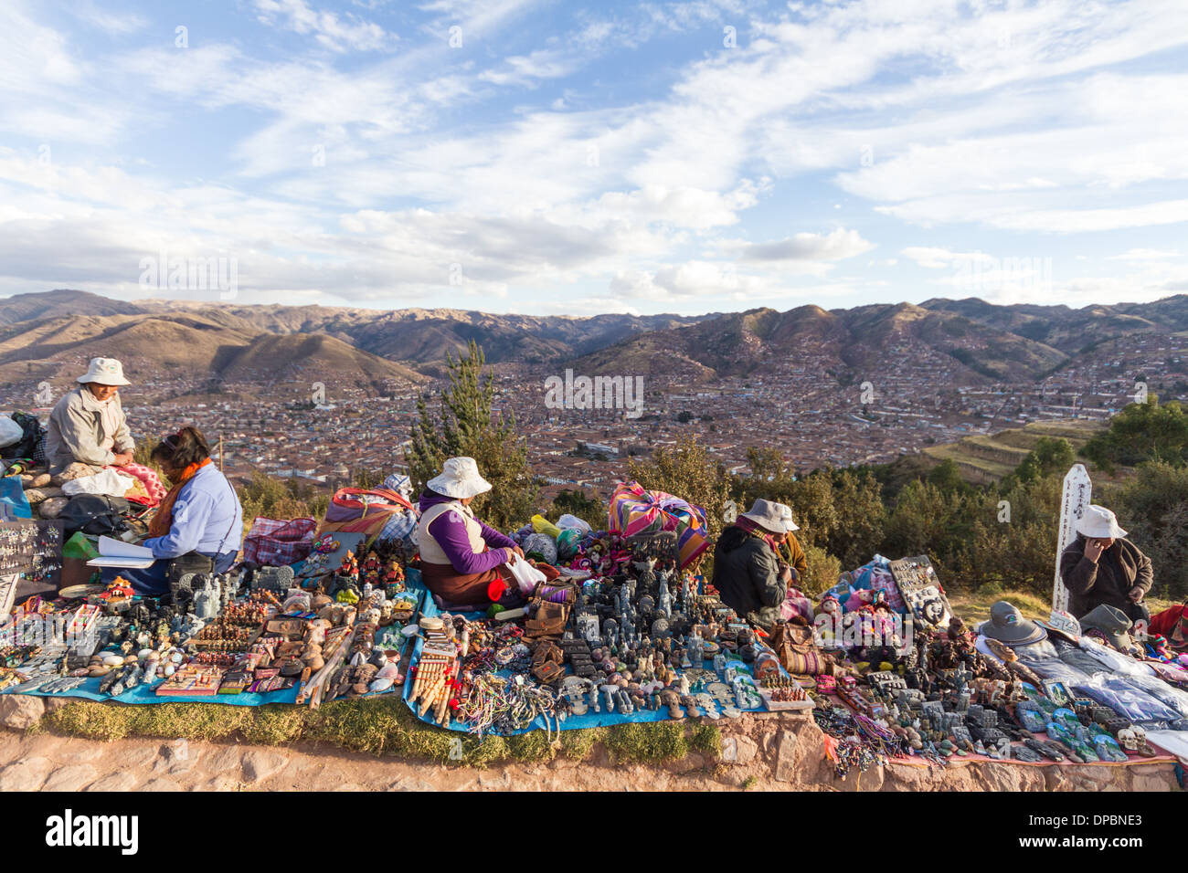 Women selling crafts on a hilltop, the city of cusco (peru) in background - Stock Image