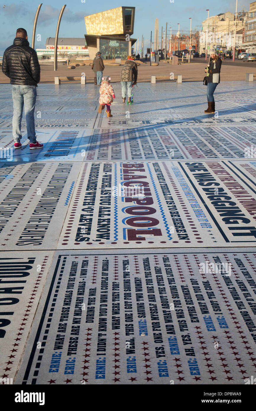 Blackpool, Lancashire, UK 11th Jan, 2014. Holidaymakers enjoying the humour and catch phrases embossed in the Comedy Pavement on Blackpool's Promenade. A celebration of comedy on an extraordinary scale. Referring to the work of more than 1,000 comedians and comedy writers, the carpet gives visual form to jokes, songs and catchphrases dating from the early days of variety to the present. The 2,200m2 work of art contains over 160,000 granite letters embedded into concrete, pushing the boundaries of public art and typography to their limits. Credit:  Mar Photographics/Alamy Live News. - Stock Image