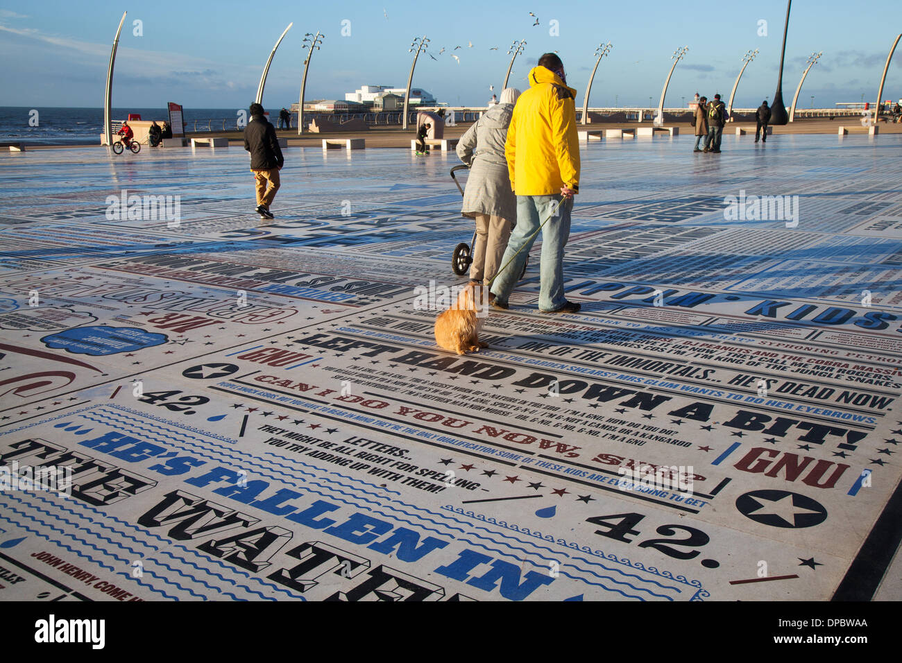 Blackpool, Lancashire, UK 11th Jan, 2014. 'The Navy lark' Holidaymakers enjoying the humour and catch phrases embossed in the Comedy Pavement on Blackpool's Promenade. A celebration of comedy on an extraordinary scale. Referring to the work of more than 1,000 comedians and comedy writers, the carpet gives visual form to jokes, songs and catchphrases dating from the early days of variety to the present. The 2,200m2 work of art contains over 160,000 granite letters embedded into concrete, pushing the boundaries of public art and typography to their limits. Credit:  Mar Photographics/Alamy Live N - Stock Image