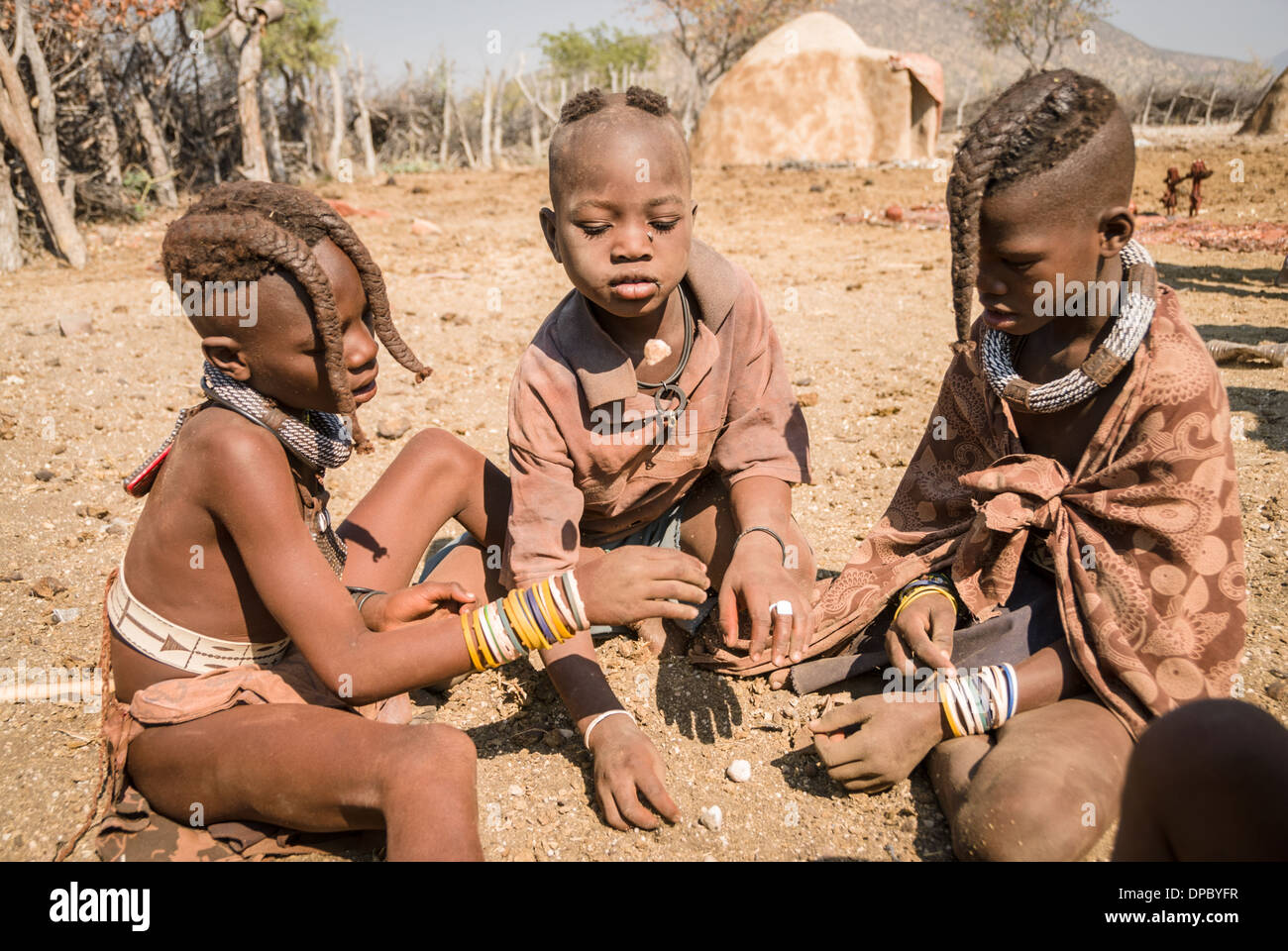 Himba children playing, village near Epupa falls, Kunene, Namibia, Africa - Stock Image