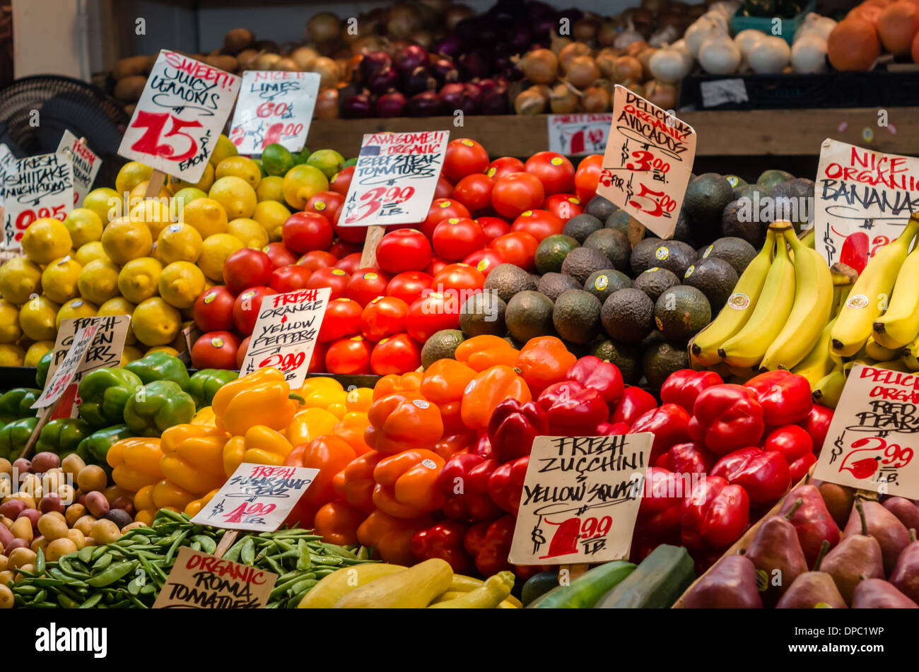 Display of fruits and vegetables with signs at a produce market stall Pike Place Market Seattle, Washington, USA - Stock Image