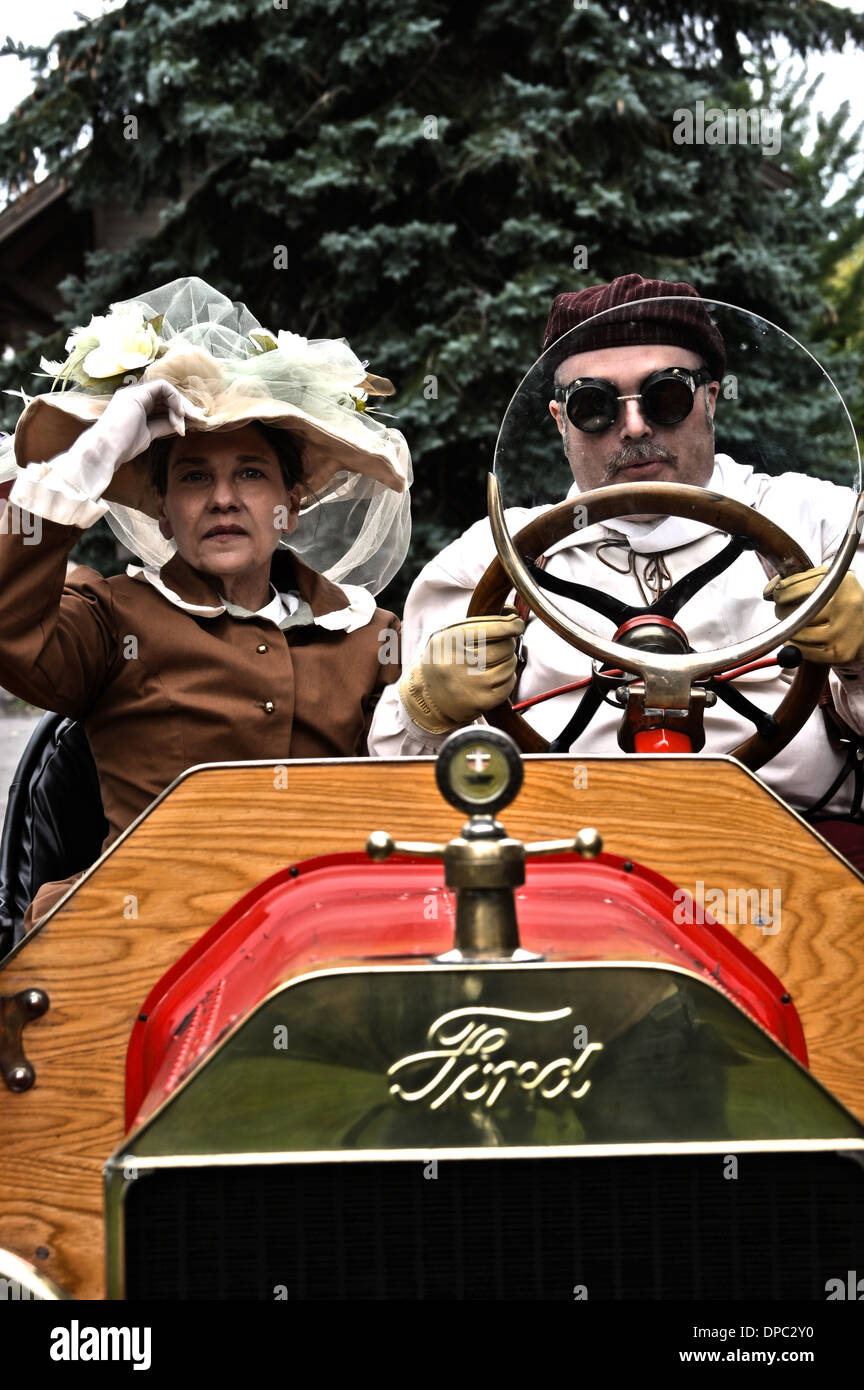 Two people driving a vintage race car - Stock Image