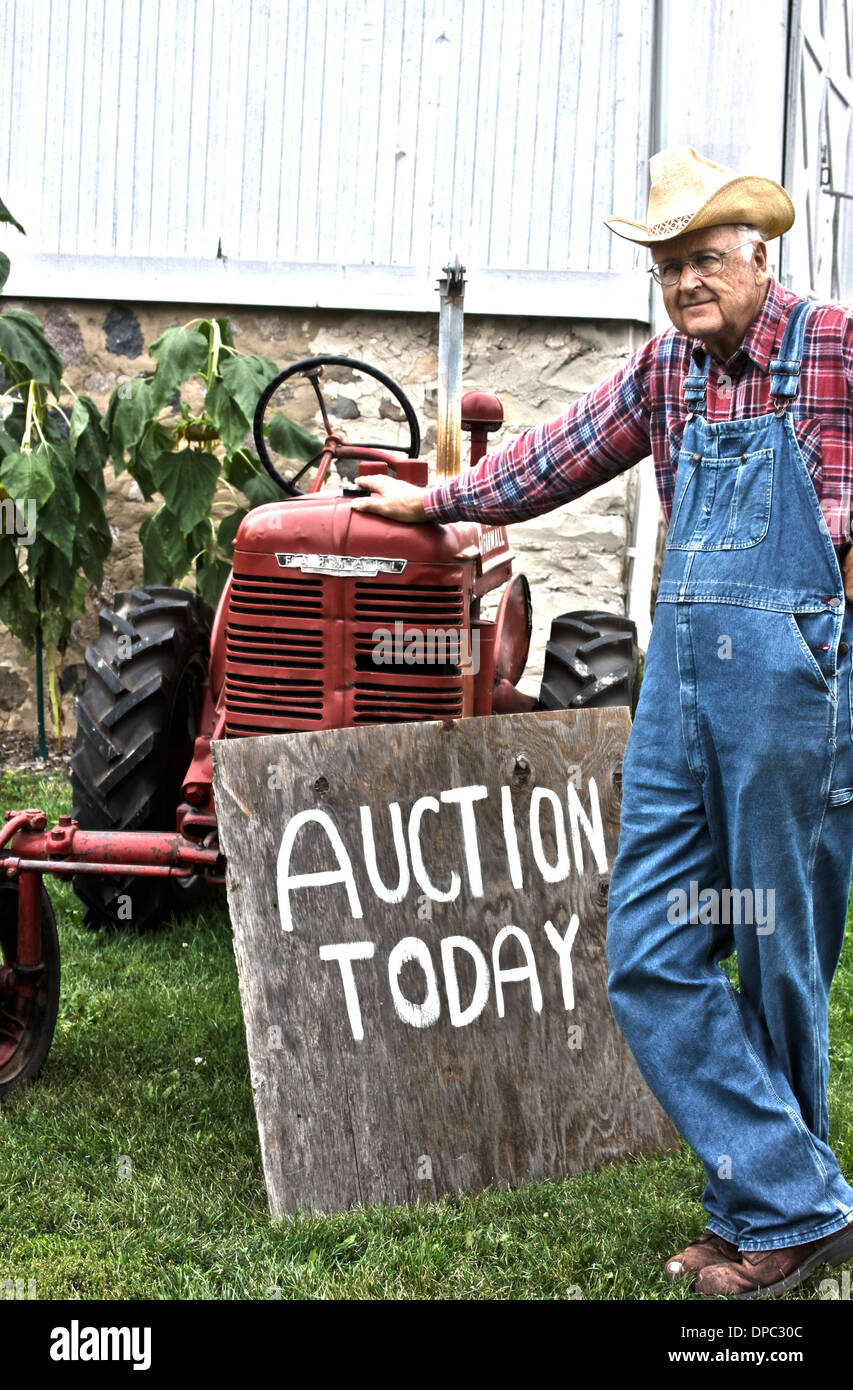Farmer in front of his tractor that he will be auctioning off today - Stock Image