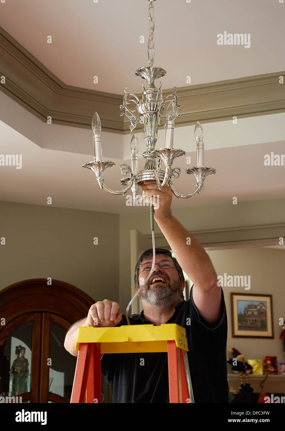 Electrician hanging a dining room light fixture - Stock Image