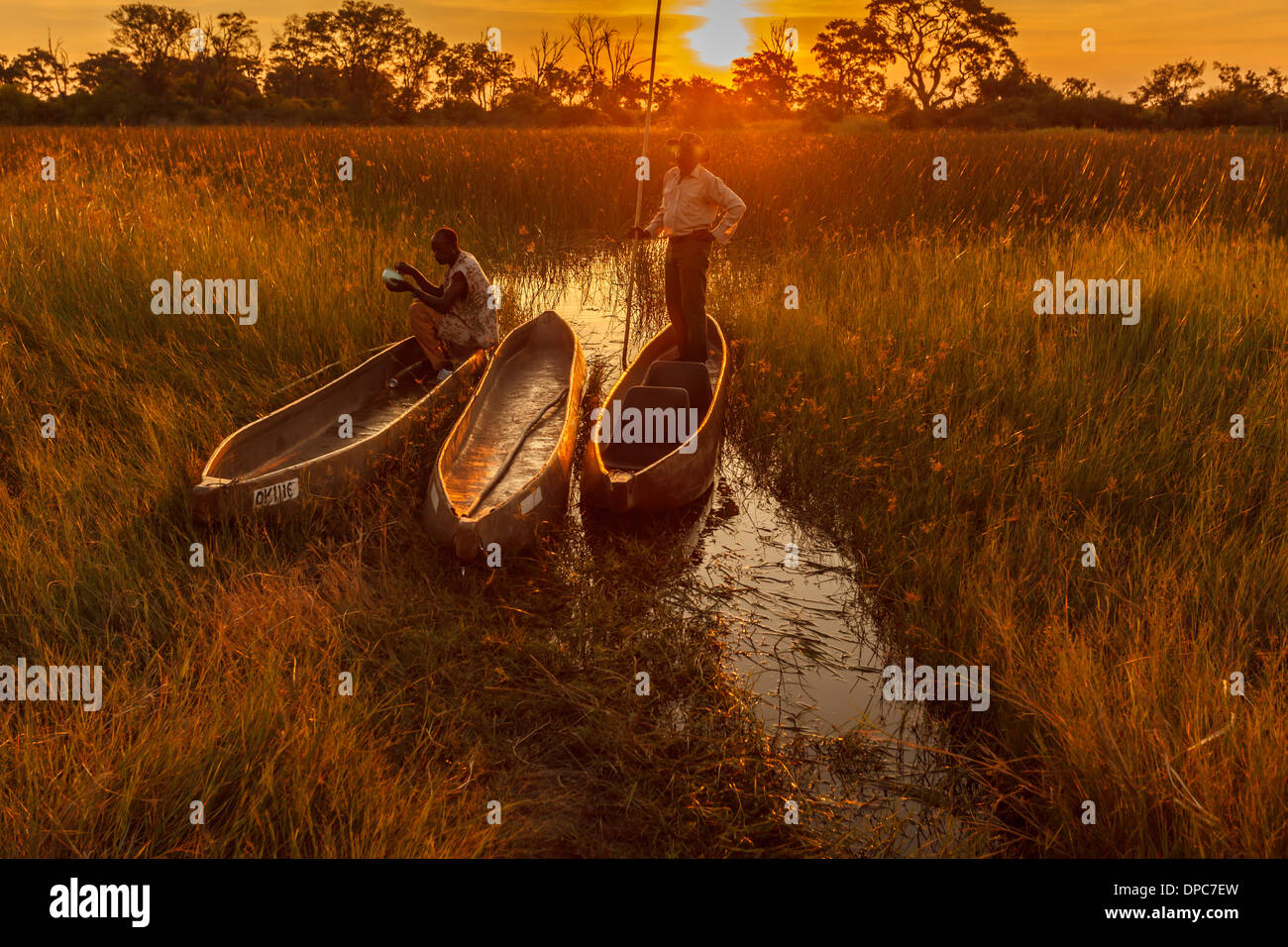 Two native men with makoro dugout canoes highlighted by orange glow of bright sun on horizon in Okavango Delta, Botswana, Africa - Stock Image