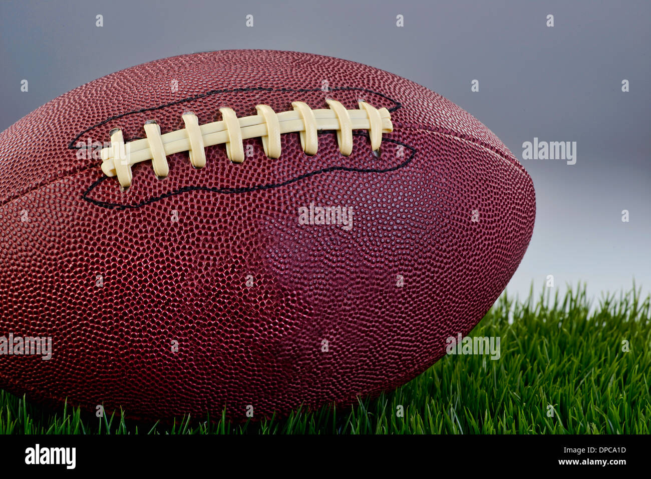 Leather football on green grass field. - Stock Image