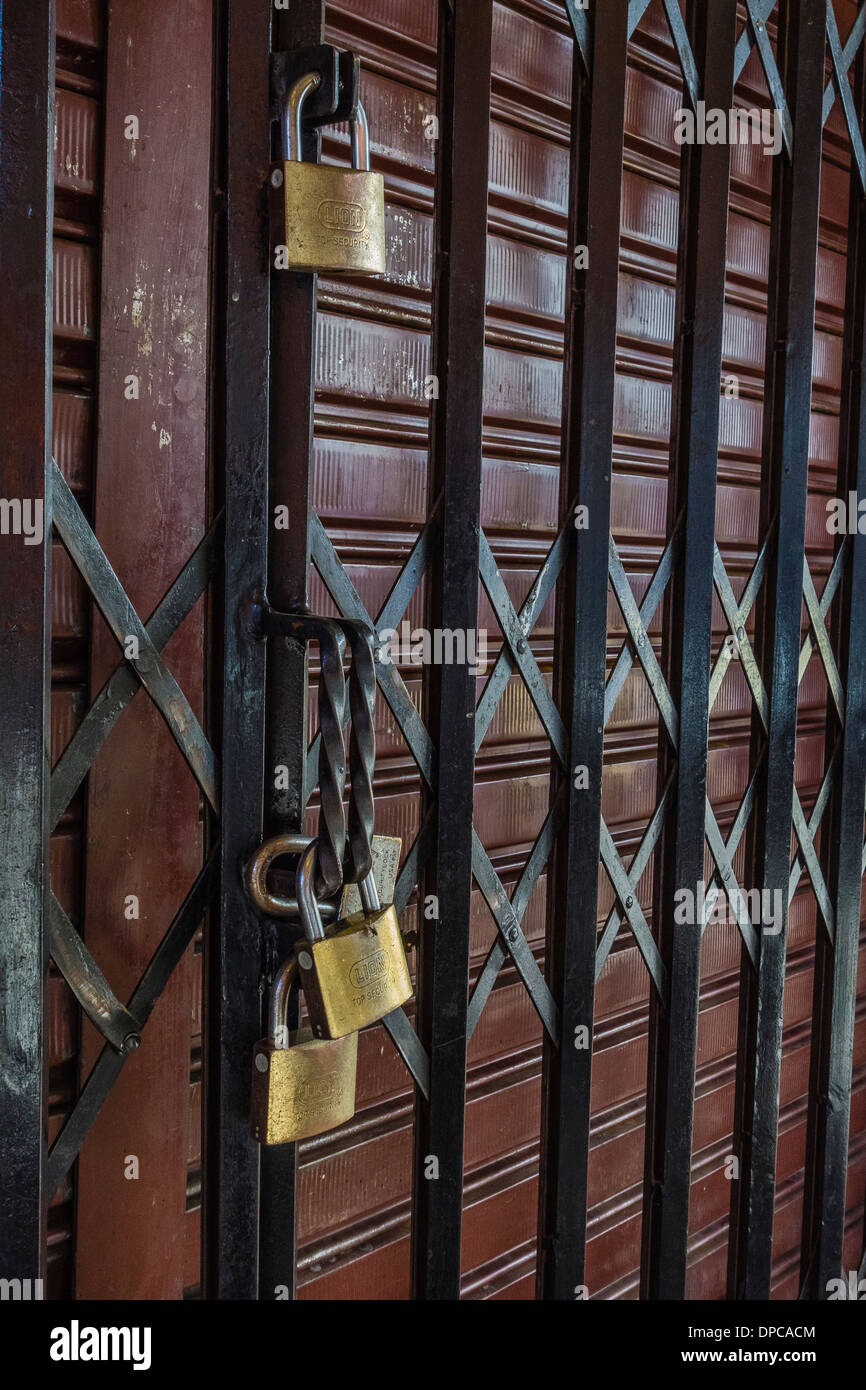 Multiple padlocks secure a store's sliding metal gate in Sucre, Bolivia. - Stock Image