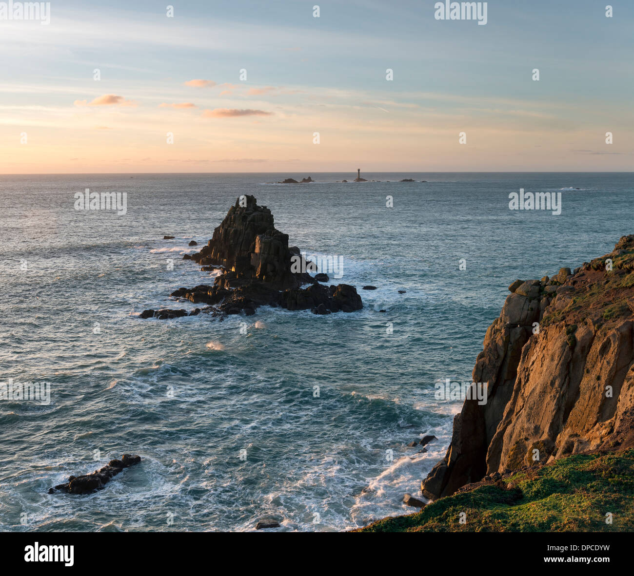 Rocky cliffs at Lands End in Cornwall with the Longships lighthouse in the distance - Stock Image