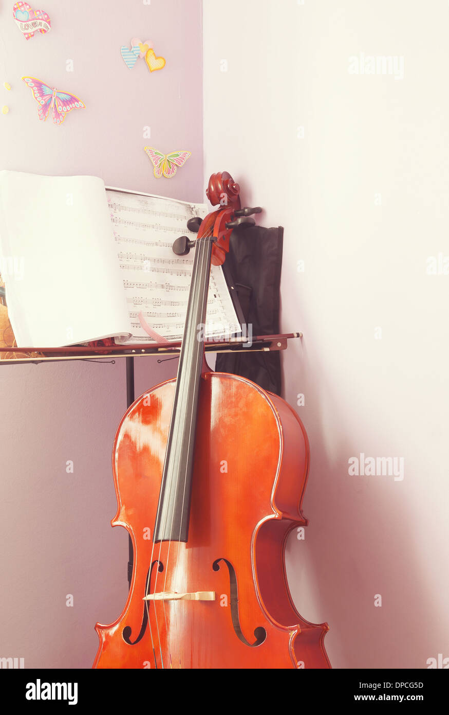 Corner of a child's room with cello and scripts ready for practice. - Stock Image