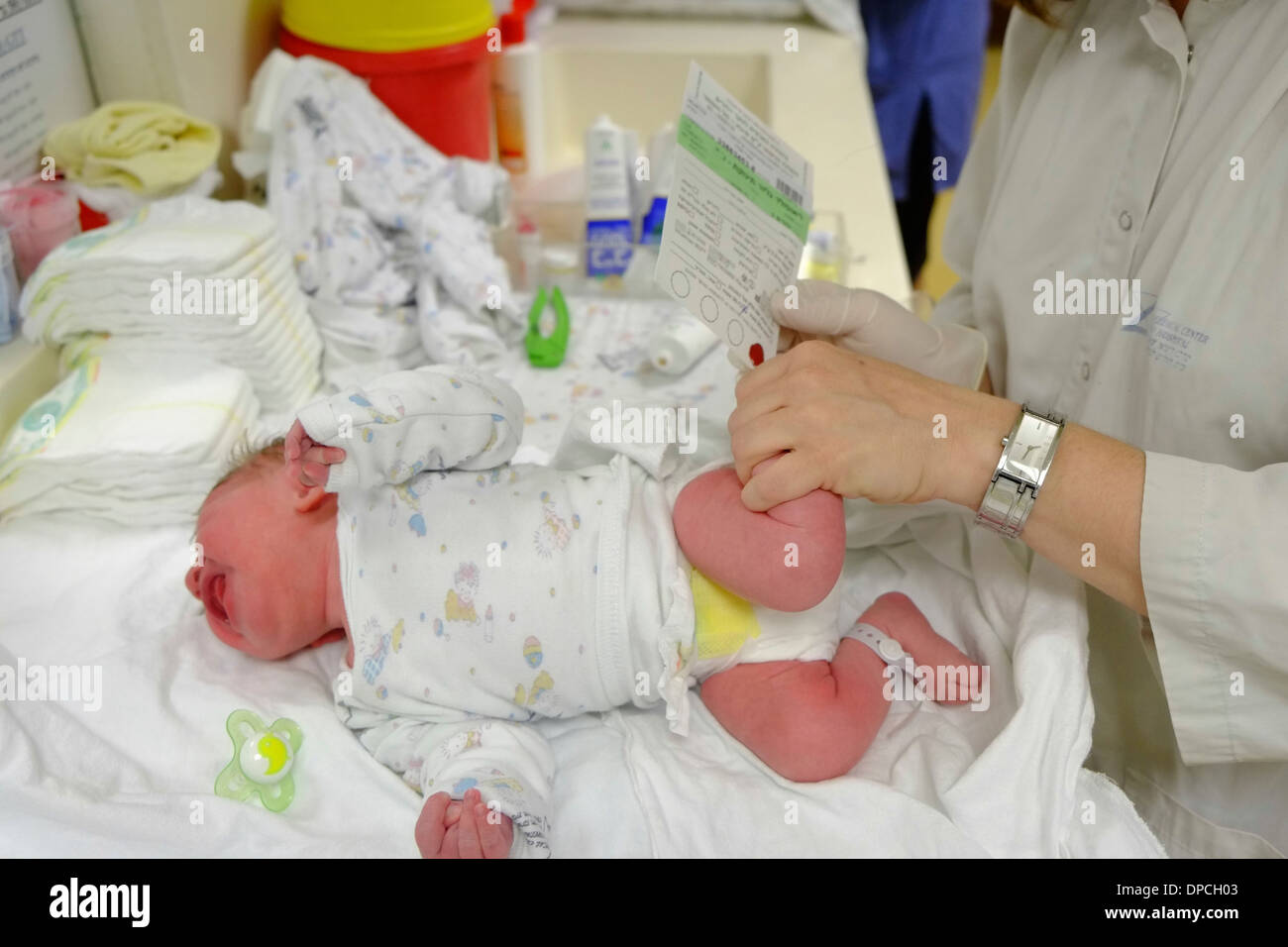 Doctor performs a blood test on a newborn infant baby in a maternity ward - Stock Image